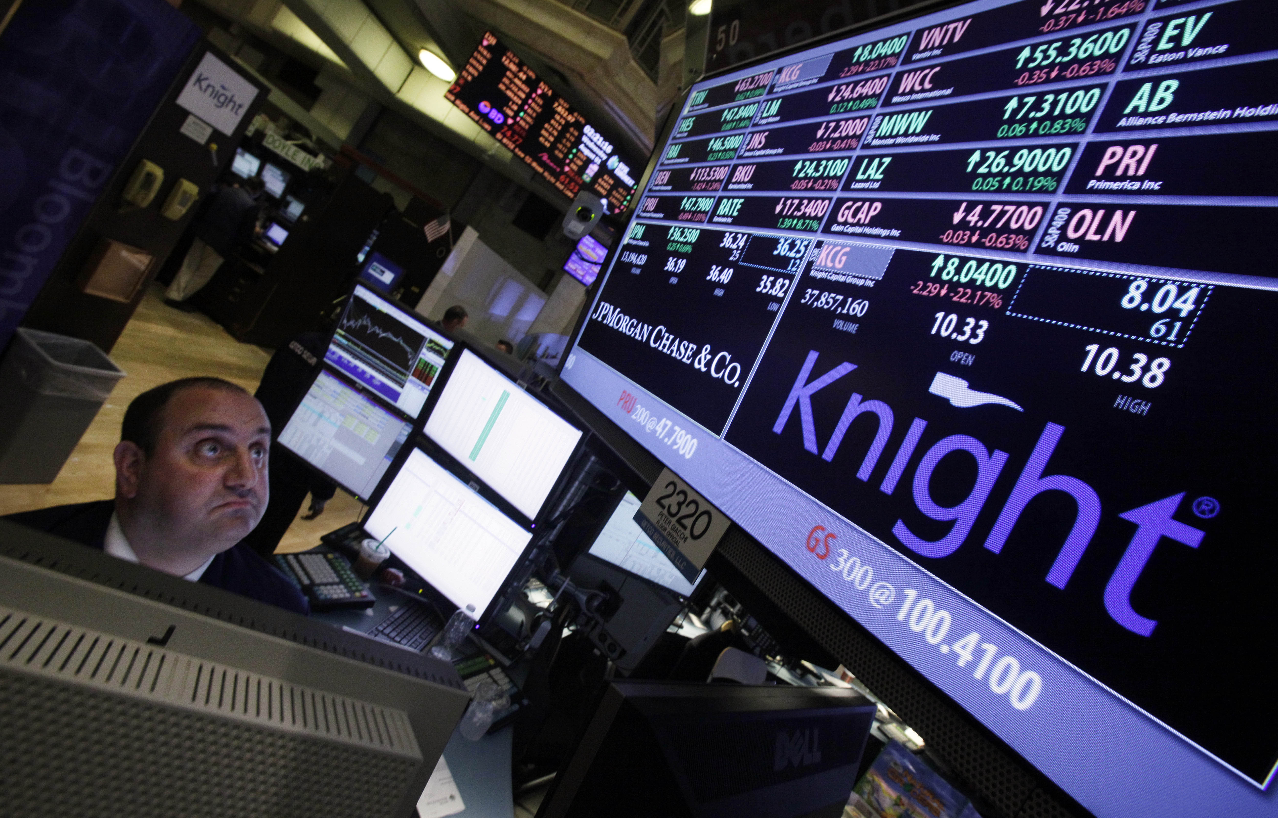 FILE - In this Aug. 1, 2012 file photo, specialist Peter Giacchi looks at the price of Knight at his post on the floor of the New York Stock Exchange. Knight Capital announced Monday, Aug. 6, 2012, that investors have agreed to supply it with $400 million in financing, which would help the trading firm stay in business after last week's disastrous software glitch that shook U.S. stock trading and jeopardized its future. (AP Photo/Richard Drew, File)