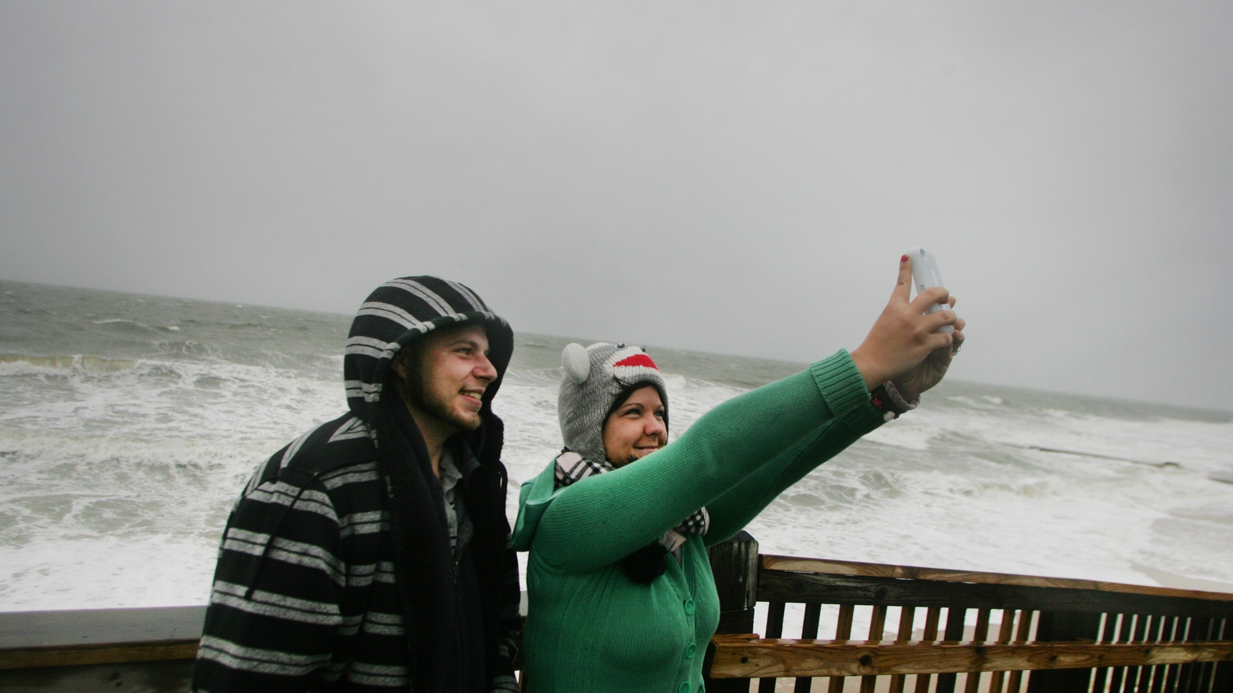 Lisa and Michael Chamberlain, a newlywed couple who is on their honeymoon, take a cell phone picture of themselves with the pounding surf from Hurricane Sandy in the background, Sunday, Oct. 28, 2012 in Virginia Beach, Va.    (AP Photo/Jason Hirschfeld)