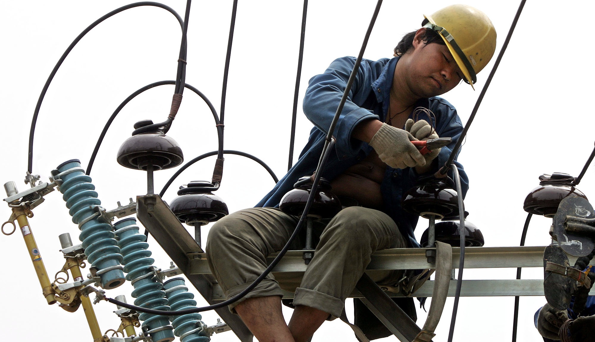 A Chinese power line worker perched on a electricity pole as he performs maintenance work in Beijing, China, Monday, July 18, 2005. The government said last month that power use in Beijing, Shanghai and other major cities has set new records and warned that portions of the country could face blackouts.   Officials said earlier that power demand this summer could exceed China's generating capacity by up to 5 percent as a booming economy and the seasonal heat waves push up energy use. (AP Photo/Ng Han Guan)
