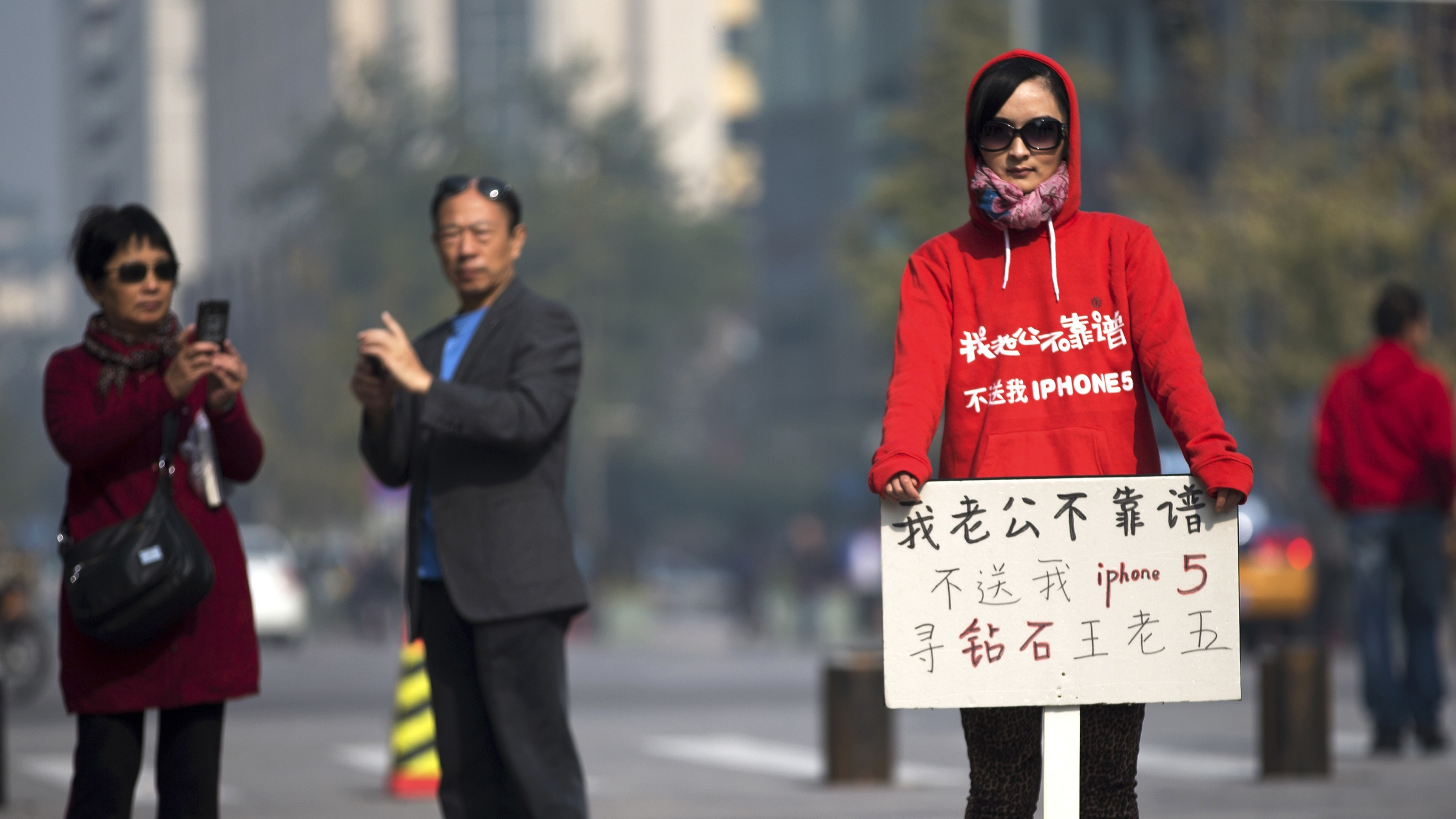 """A couple take photo of a Chinese woman holds a sign reads """"My husband not reliable, don't buy me iPhone 5, looking for rich man"""" stands near the newly opened Apple Store in Wangfujing shopping district in Beijing Saturday, 20, 2012. (AP Photo/Andy Wong)"""