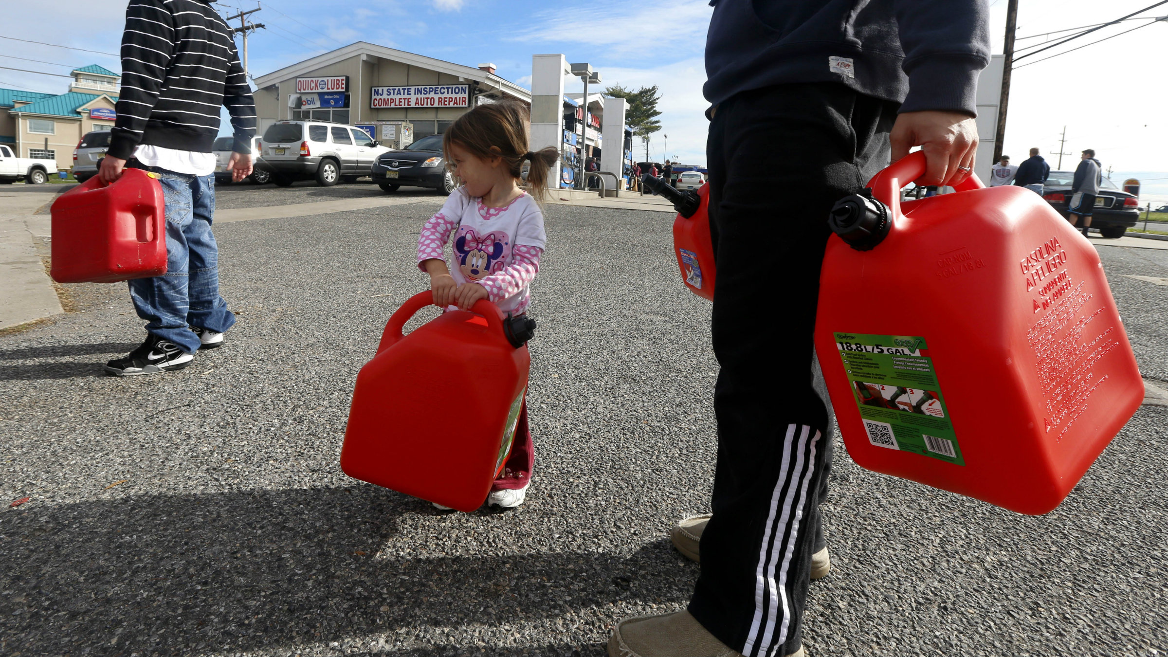 Sandy's effects, big and small: Residents of New Jersey try to fill up containers with petrol.