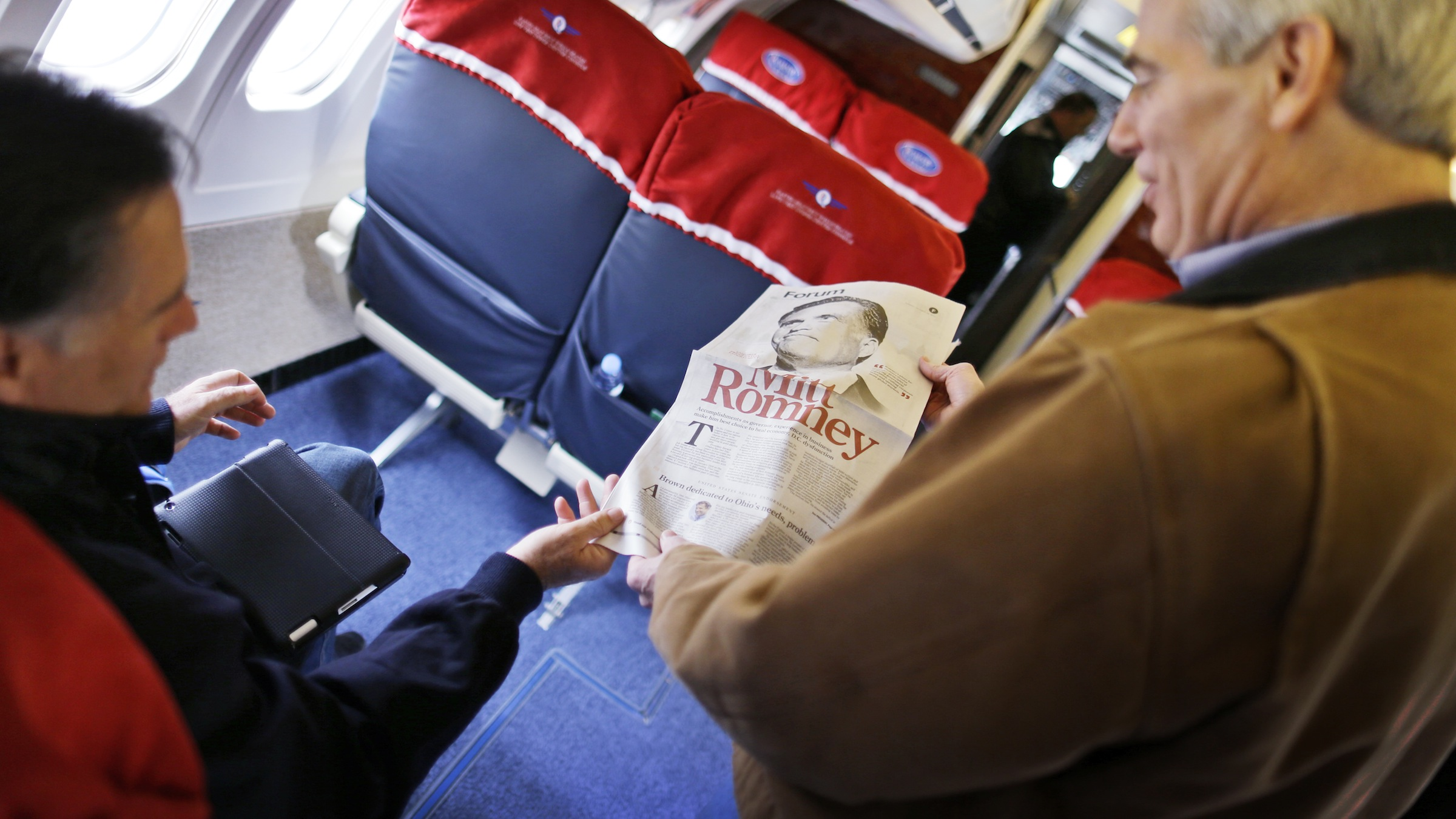Republican presidential candidate and former Massachusetts Gov. Mitt Romney is shown a page from a newspaper which endorsed him by Sen. Rob Portman, R-Ohio, after he landed at Dayton International Airport in Vandalia, Ohio, Sunday, Oct. 28, 2012. (AP Photo/Charles Dharapak)
