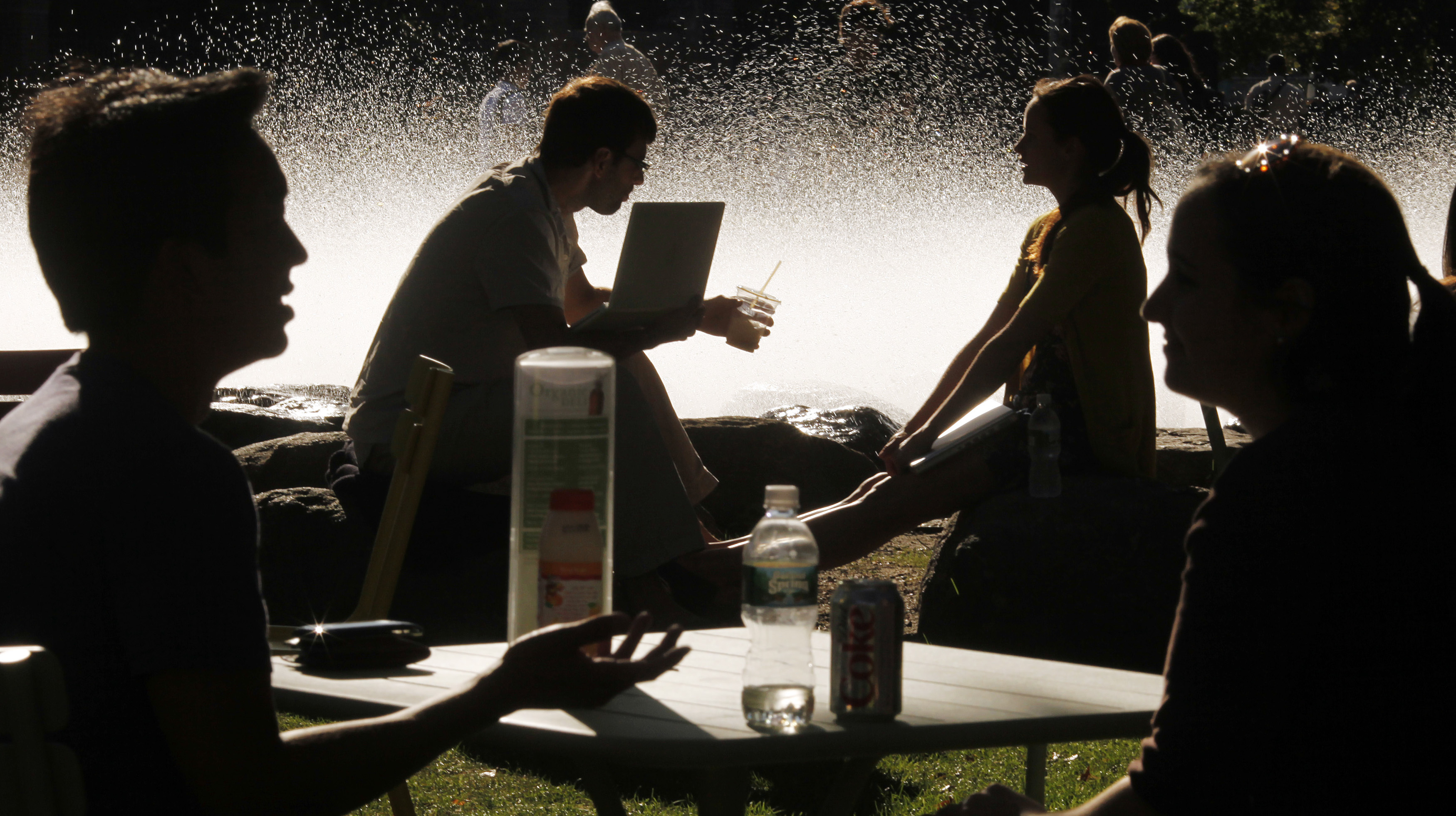 Students and visitors sit in front of a fountain at Harvard University in Cambridge, Massachusetts September 21, 2009.