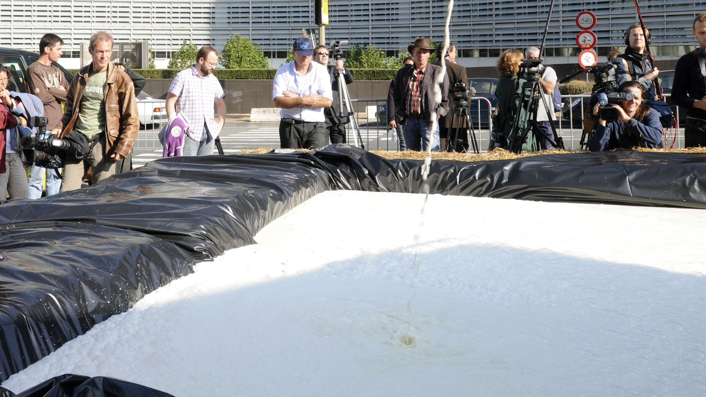 Belgian milk producers fill up a makeshift pool with milk in front of the European Union Commission headquarters, in Brussels, Monday Sept. 21, 2009. Dairy farmers dumped thousands of litres of milk outside the headquarters of the European Union in Brussels on Monday to symbolise ongoing Europe-wide protests for price controls on milk to help struggling producers. More than 5,000 litres of milk was dumped into an artificial lake made from hay bales. (AP Photo/Thierry Charlier)