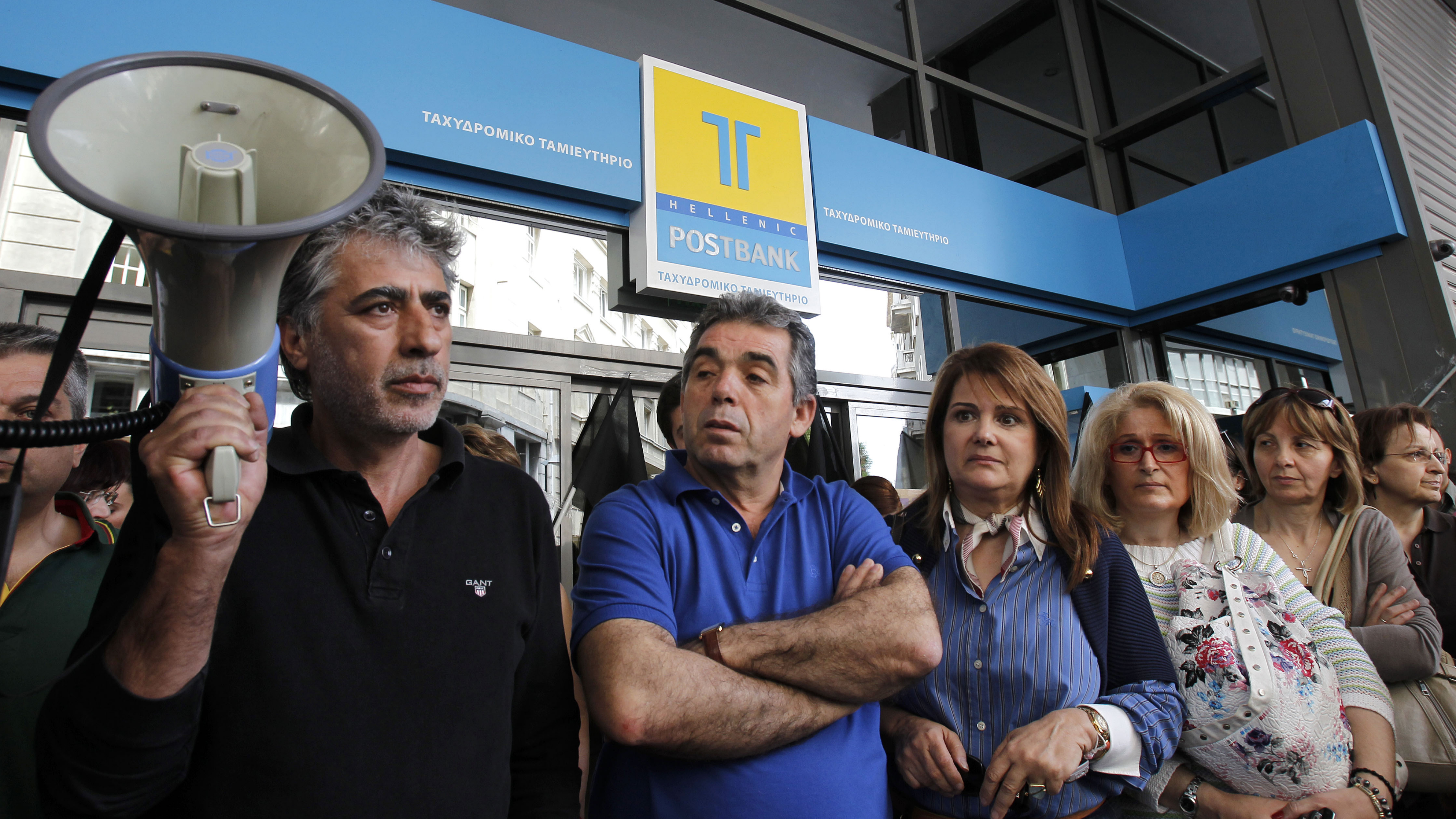 Protesting employees of the state-run Hellenic Postbank block the entrance to the headquarters of the bank in central Athens, on Wednesday, May 25, 2011. The government in crisis-hit Greece has promised to privatize the bank in a massive sale of state assets aimed at raising 50 billion euros by the end of 2015, to help pay the country's massive national debt. (AP Photo/ Petros Giannakouris)