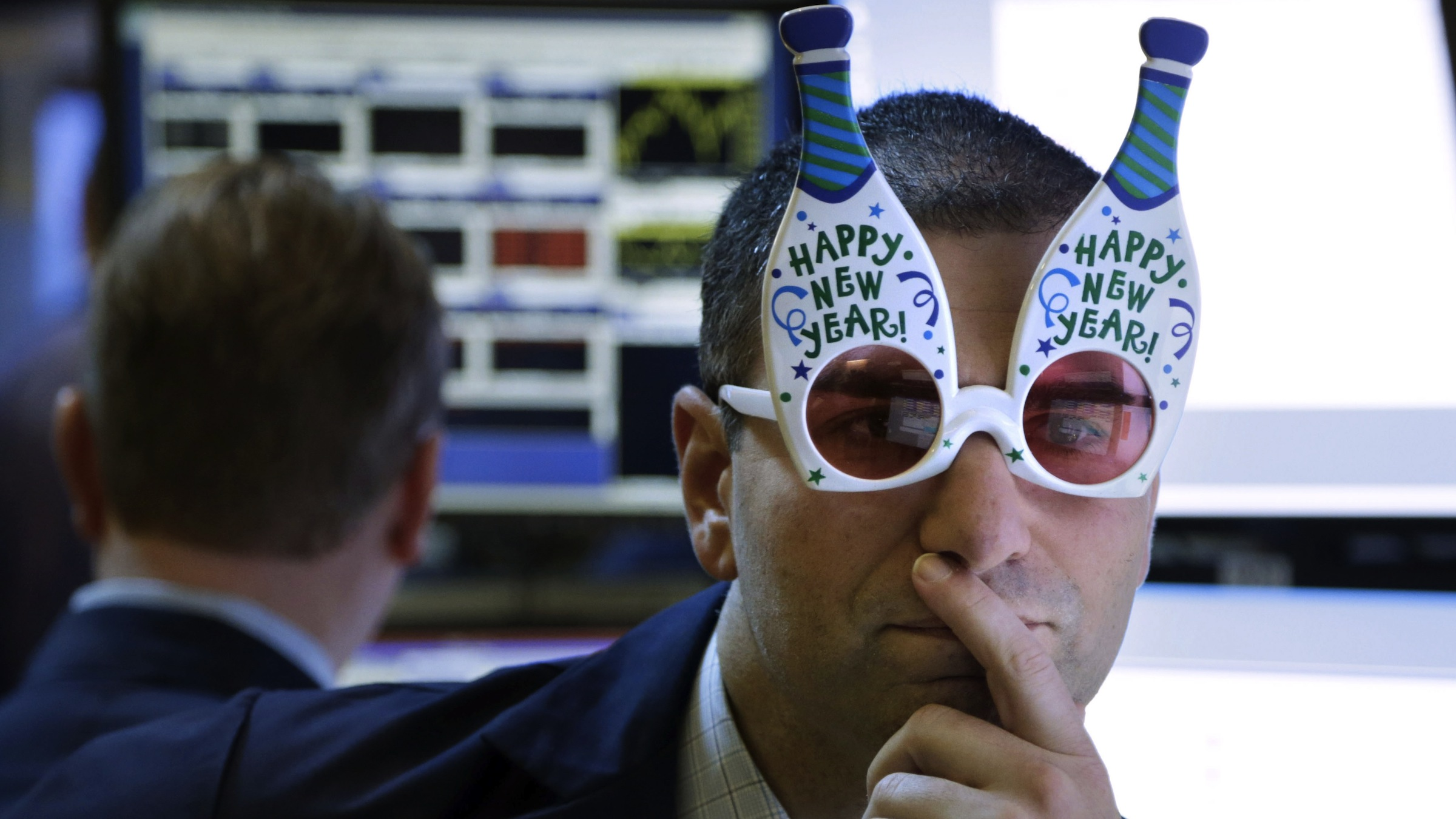 "A trader wearing ""Happy New Year"" glasses works on the floor at the New York Stock Exchange in New York, on Monday, Dec. 31, 2012. The stock market struggled for direction Monday morning after five days of losses, with the ""fiscal cliff"" just hours away and lawmakers yet to reach a solution. (AP Photo/Seth Wenig)"