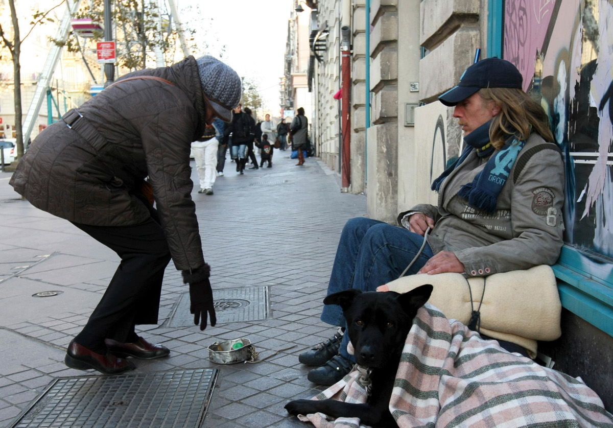 A woman gives money to a homeless man in Marseille.