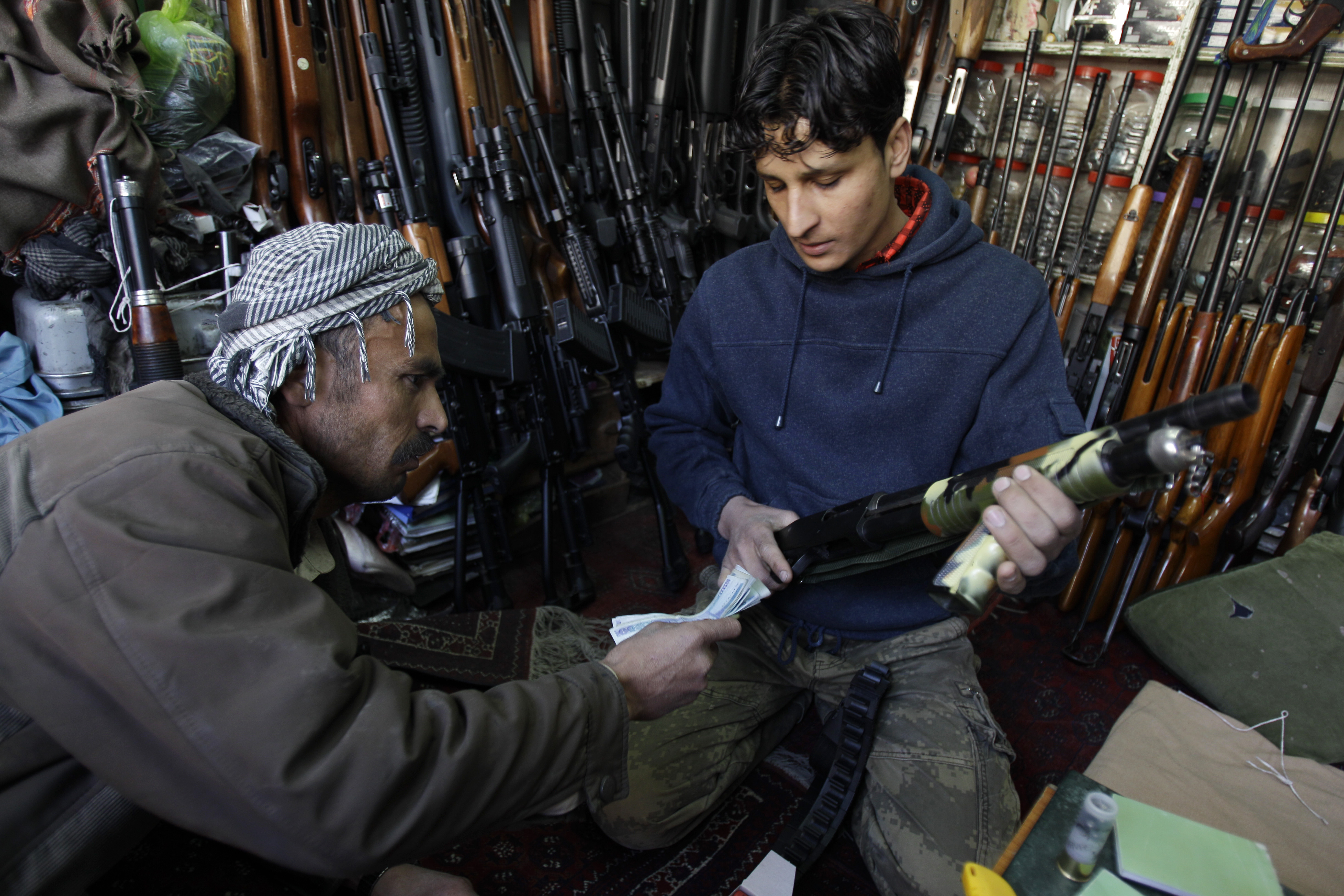 """Saeed Sarwar, left, buys a Pakistan made gun for about $ 110 (76 eur) to protect his family and home from attack by drug addicts in the """"Ghala Now"""" suburb in Kabul, Afghanistan, Tuesday April 12, 2011. (AP Photo/Kamran Jebreili)"""