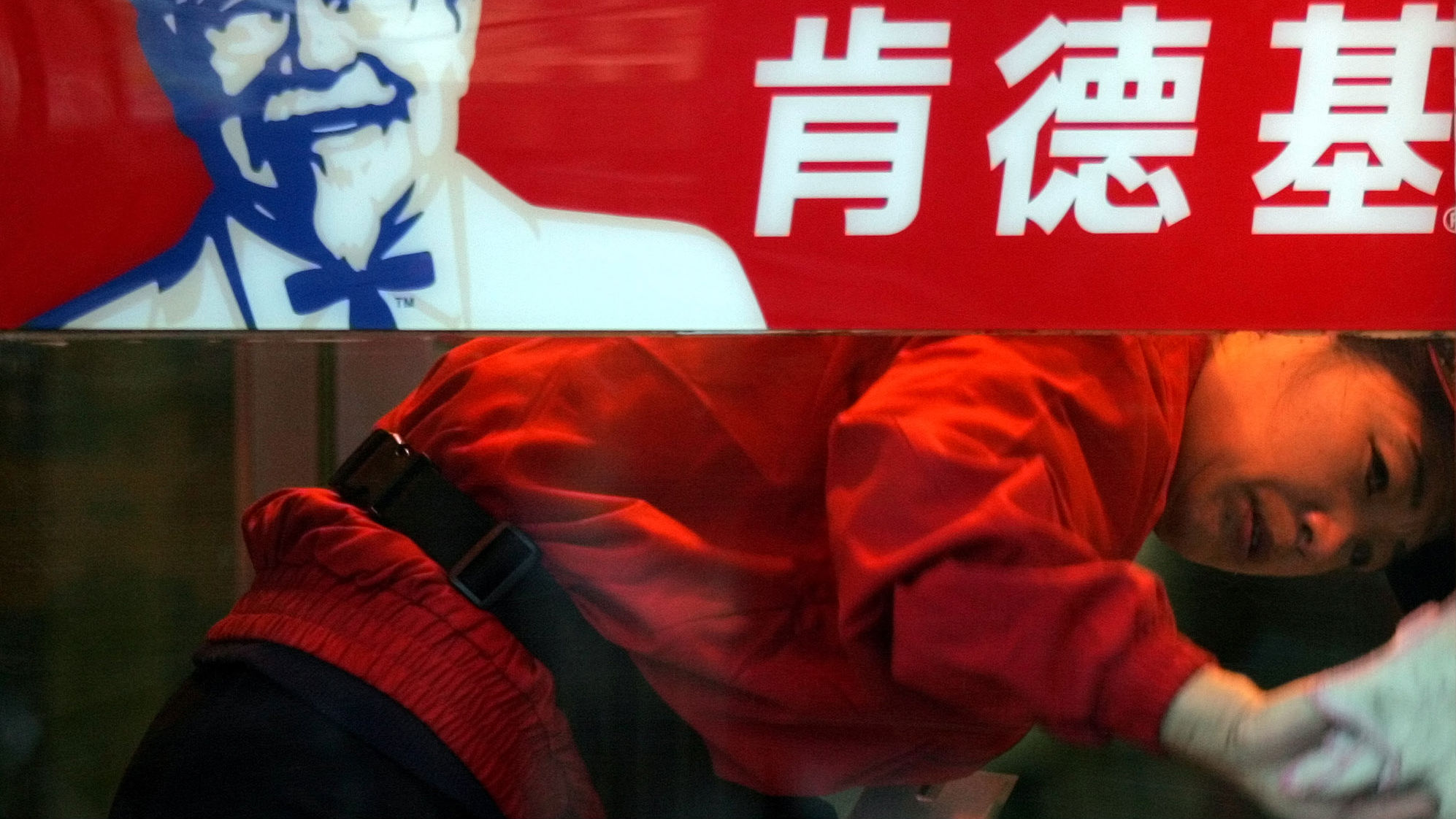 A Chinese worker cleans the glass door of a KFC restaurant in Beijing Tuesday, Jan 18, 2005. China's relentless appetite for the colonel's chicken has KFC on a building boom in the world's most populous country, with 1,200 locations, soaring profits and a menu that mixes in bamboo shoots and lotus roots.