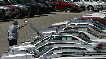 A man looks at a used car