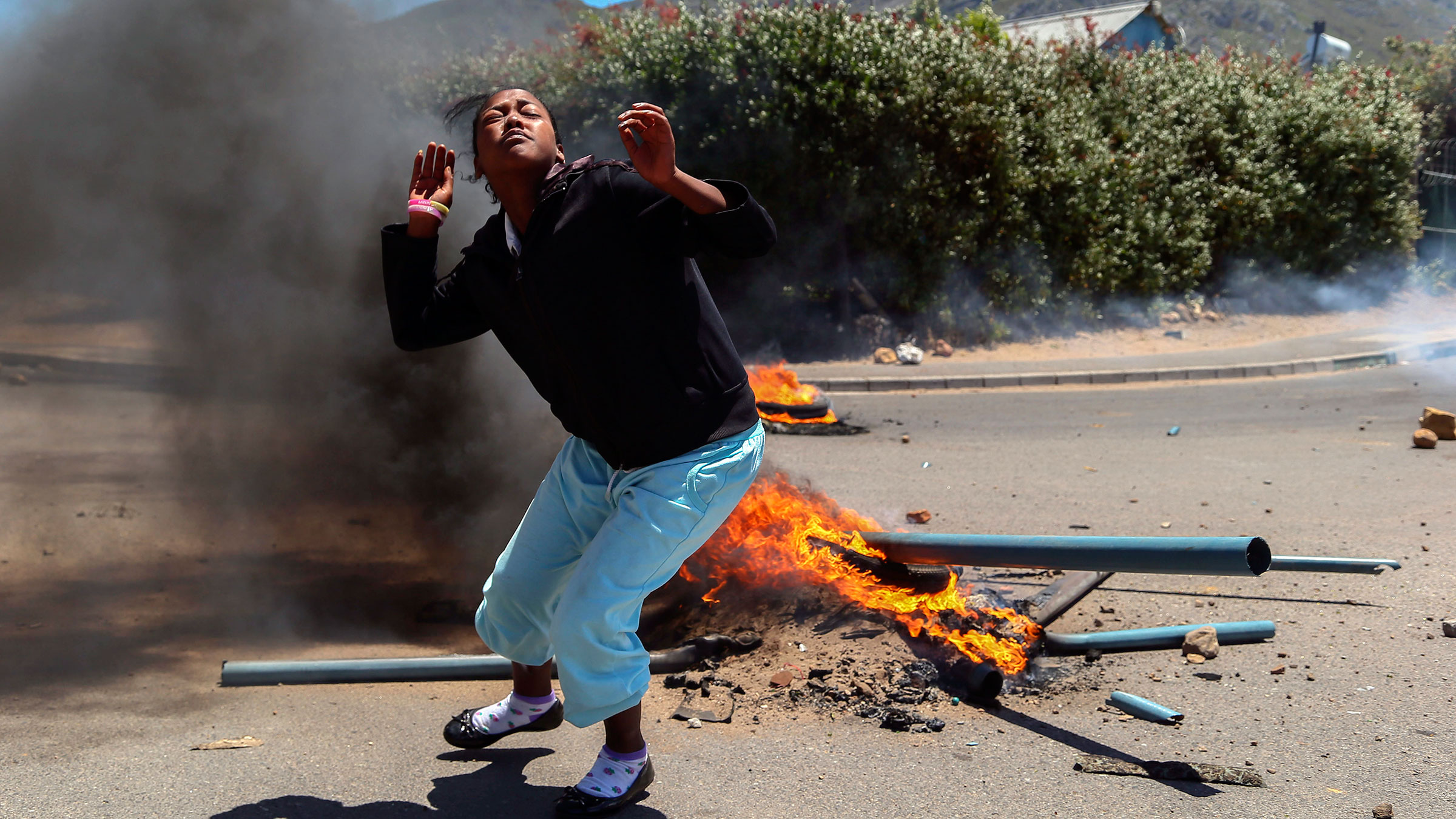 Dec. 4, 2012. A woman runs from a burning barricade during a farm workers strike in the wine producing valley of Franschhoek, outside Cape Town, South Africa.