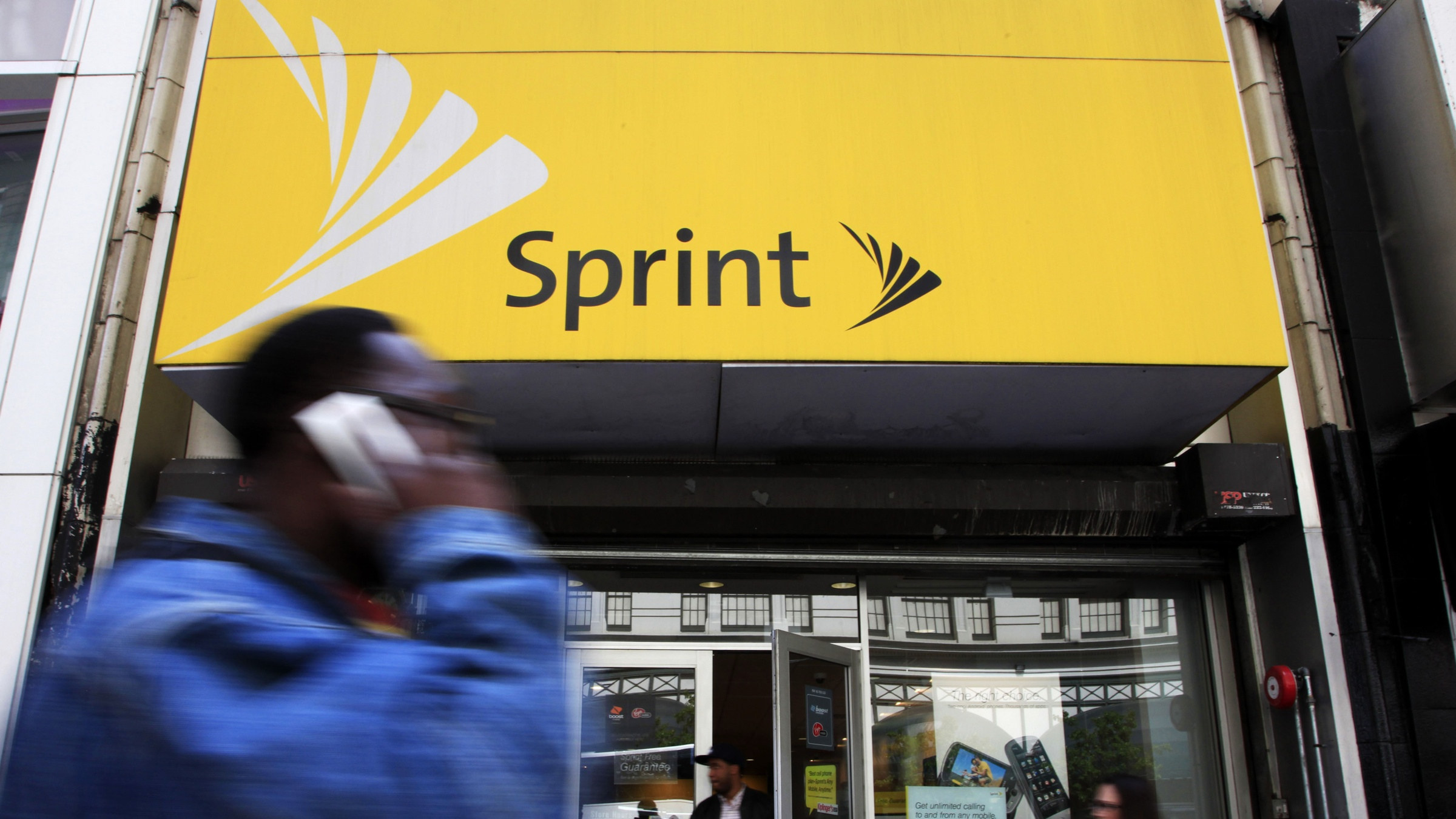 A man using a cell phone walks past a Sprint store, Tuesday, April 27, 2010 in New York. Sprint Nextel Corp. releases quarterly results Wednesday. (AP Photo/Mark Lennihan)