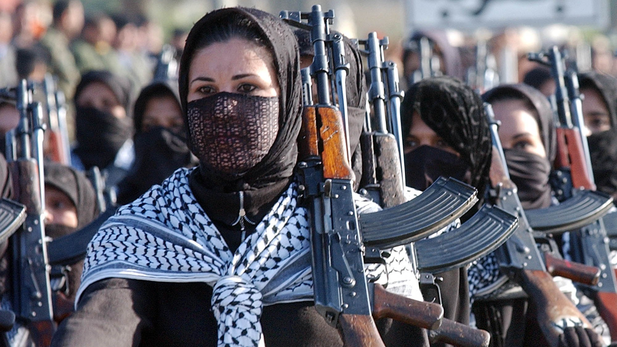 Iraqi women army volunteers holding AK-47 assault rifles march during a military parade held in Diala province 70 Kilometers/50 miles northeast of Baghdad, Iraq Tuesday, Jan. 7, 2003. Thousands of volunteers participated in the parade to mark the 82nd anniversary of the founding of the Iraqi army. (AP Photo/Hussein Malla)