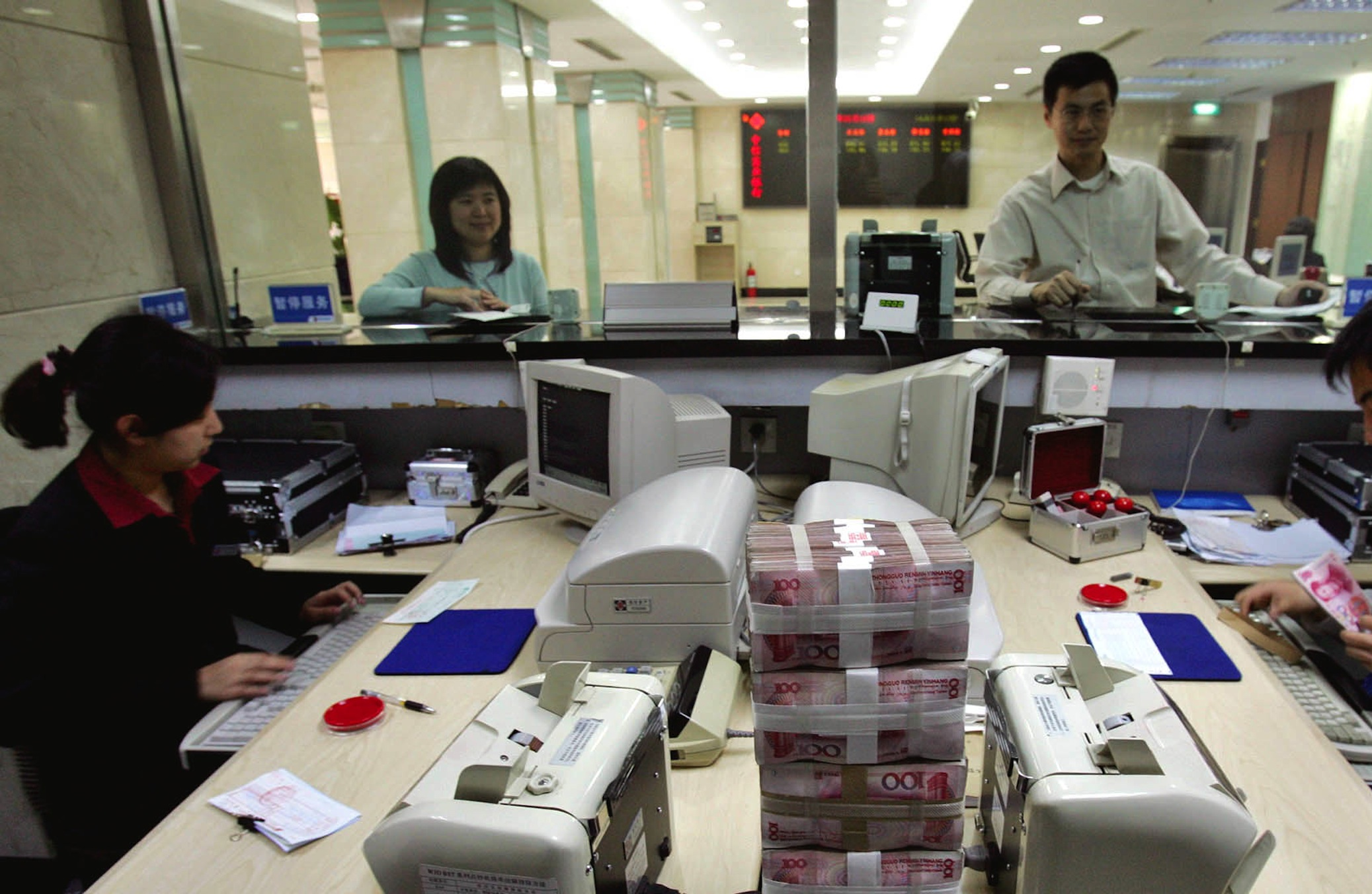 A Chinese bank employee counts 100 Yuan bills as a colleague takes care of a customer at a bank in Beijing Monday, April 18, 2005.  Given China's growing role as an export power, a decision by Beijing to let the Chinese currency rise in value against the U.S. dollar after 11 years of keeping it fixed at about 8.28 yuan per dollar could have myriad implications for consumers, manufacturers and government decision makers worldwide.