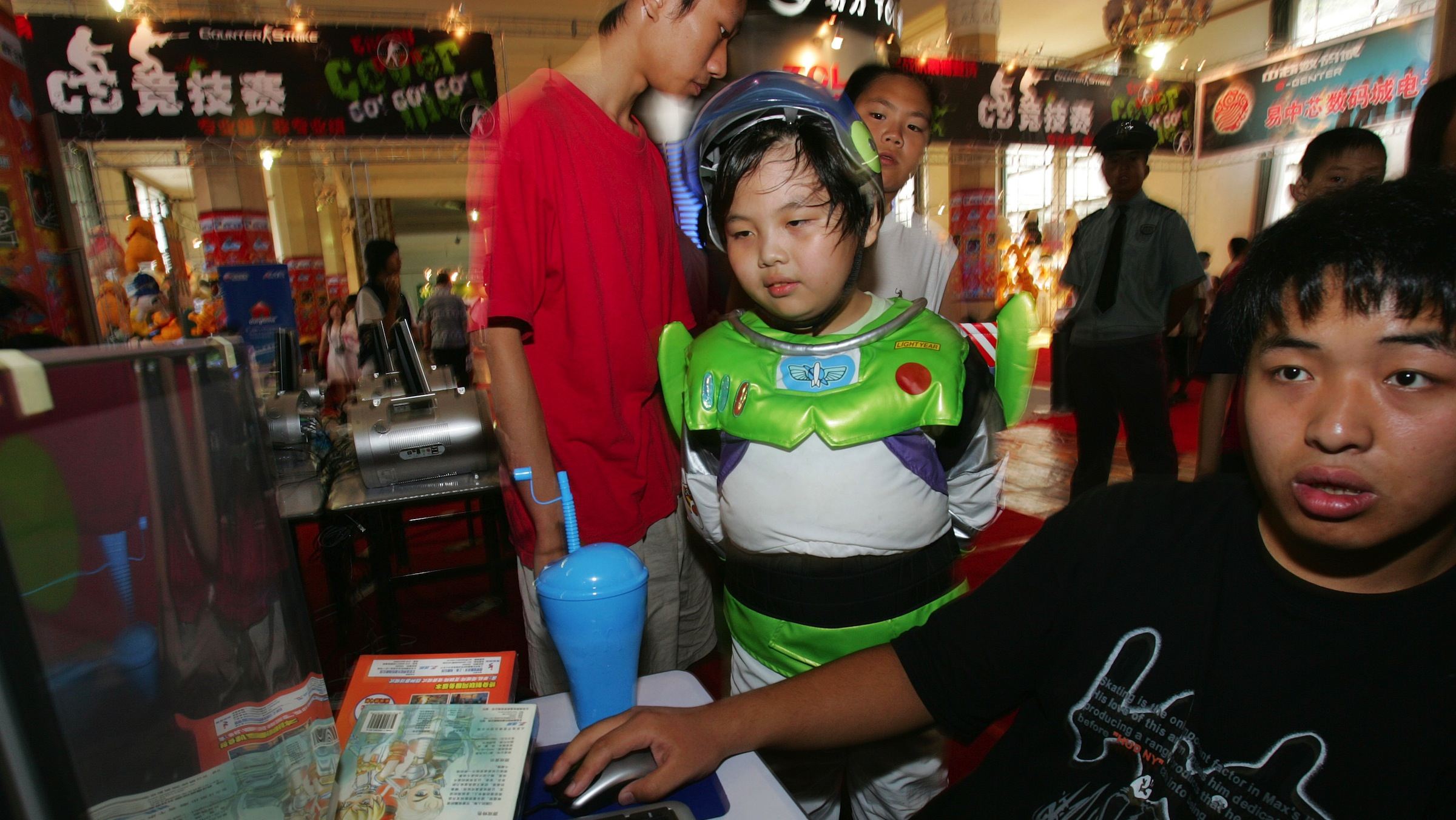 """A Chinese boy dressed like the American cartoon character Buzz Lightyear watches a fellow video game player try his luck at the the game """"Counter Strike"""" as a Chinese security guard stands guard nearby at the Splendid dress carnival cartoon festival being held at the Beijing Military Museum in the Chinese capital Thursday Aug. 4, 2005. China will bar new foreign television channels and step up censorship of imported programming, the Culture Ministry announced, adding to a sweeping effort to tighten the communist government's controls over popular culture. The government also will ban new licenses for companies to import newspapers and magazines, electronic publications, audiovisual products and children's cartoons.(AP Photo/Elizabeth Dalziel)"""