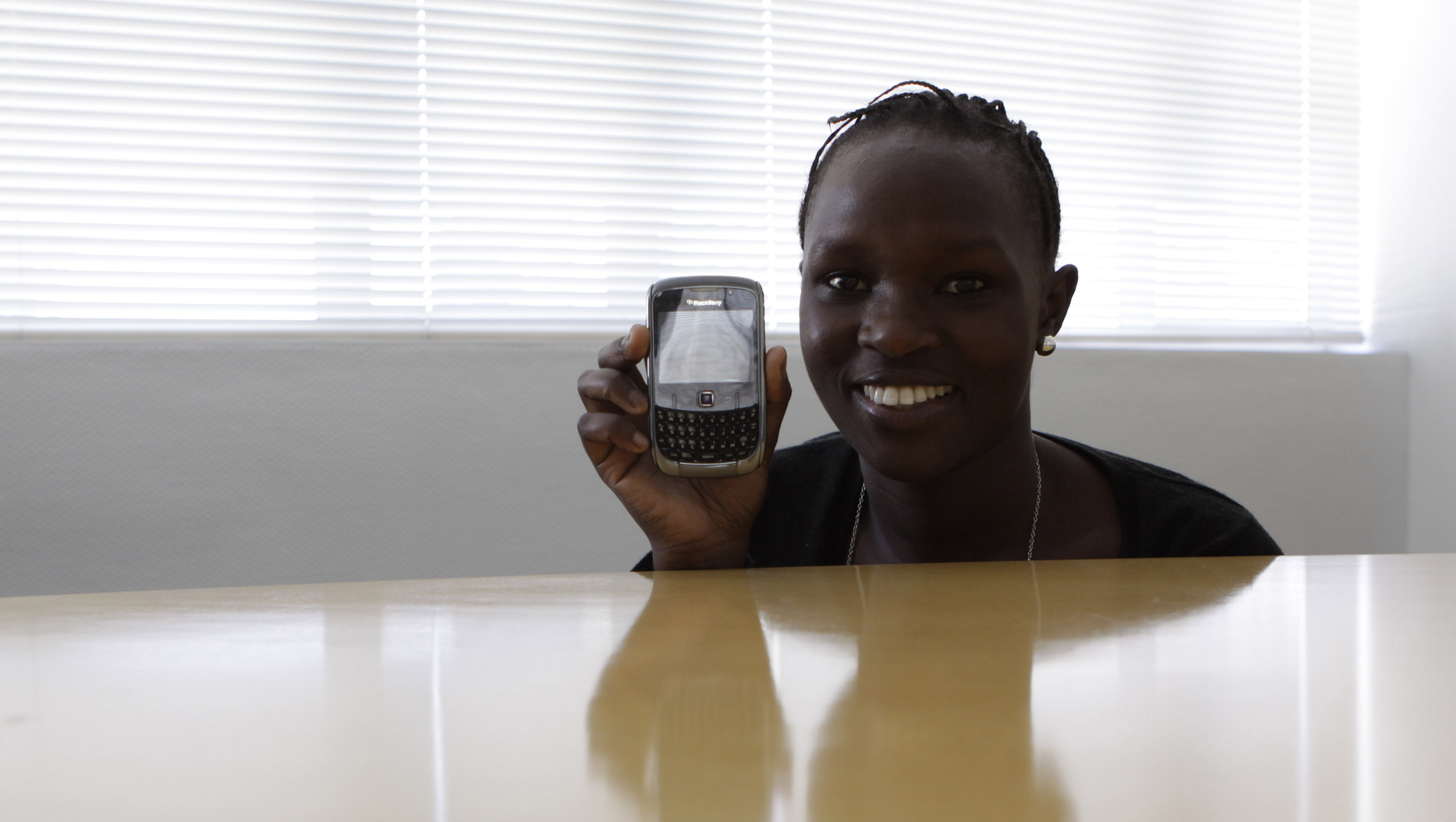 In this photo taken Tuesday, Nov. 8, 2011, Gertrude Kitongo, poses with her Blackberry mobile phone in Johannesburg. Kitongo cherishes a cell phone as a link to family and friends, and also sees it as a radio, a library, a mini cinema, a bank teller and more. (AP Photo/Denis Farrell)