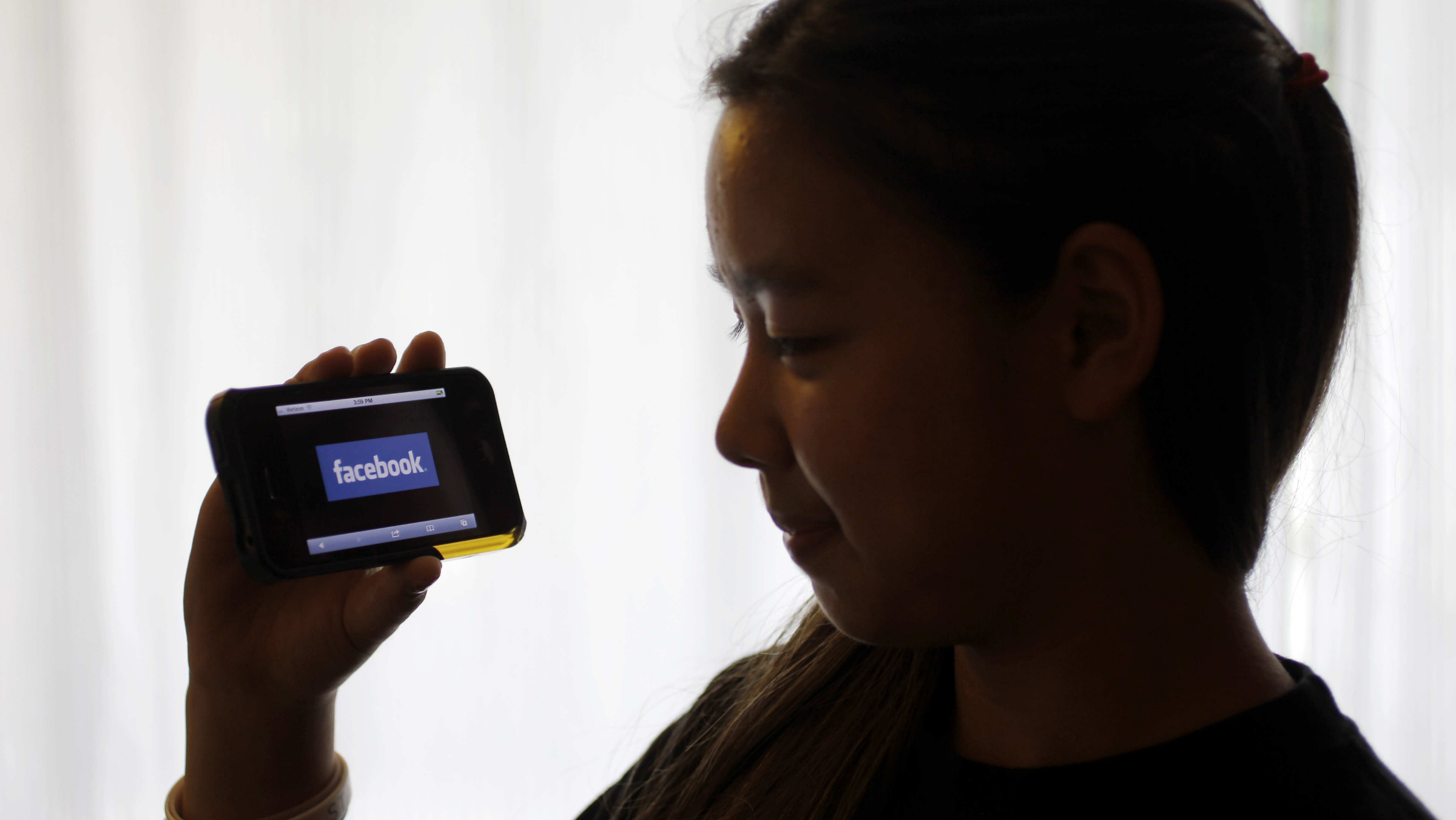 An unidentified 11-year-old girl holds up her iPhone with the Facebook website displayed at her home in Palo Alto, Calif., Monday, June 4, 2012. Though Facebook bans children under 13, millions of them have profiles on the site by lying about their age. The company is now testing ways to allow those kids to participate without needing to lie. This would likely be under parental supervision, such as by connecting children's accounts to their parents' accounts. (AP Photo/Paul Sakuma)