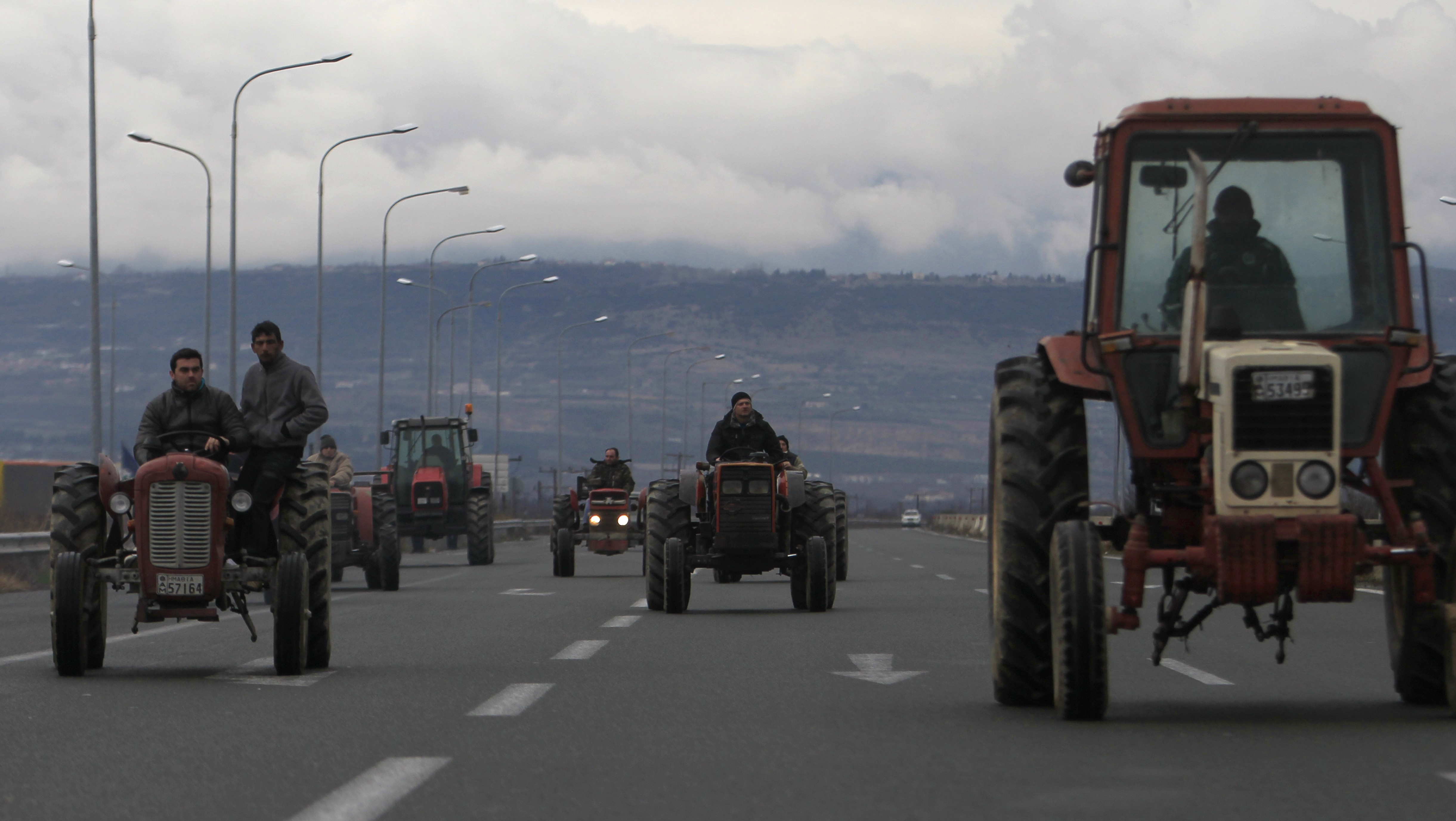 """Farmers drive their tractors on Egnatia highway near the northern Greek city of Veria, Greece, on Saturday, Jan. 26, 2013. Farmers from Veria used their tractors to block Greece's northern highway """"Egnatia"""" for about an hour. Some farmers are complaining they have not yet received state subsidies while others say compensation for natural disasters that have hurt their crops is too low.(AP Photo/Nikolas Giakoumidis)"""