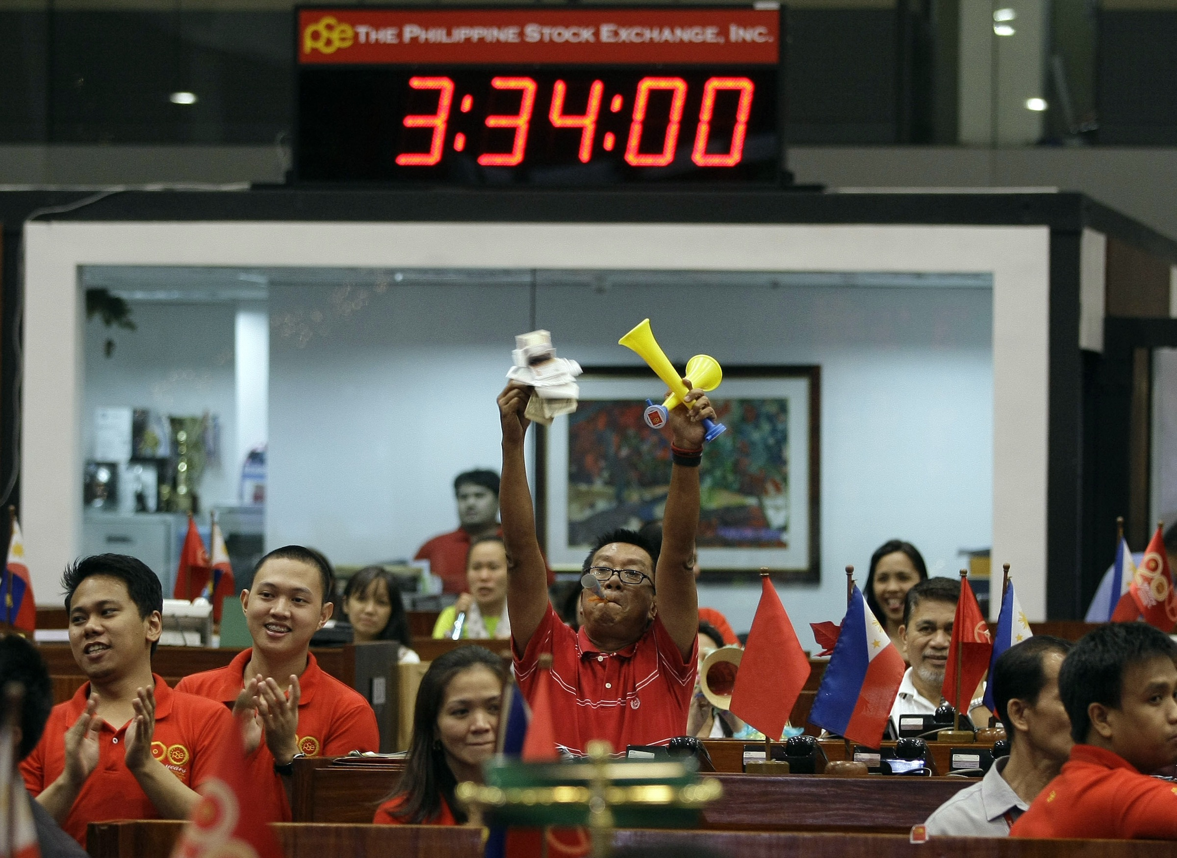 Filipino traders gesture as trading closes for the year at the Philippine Stock Exchange in the financial district of Makati, south of Manila,