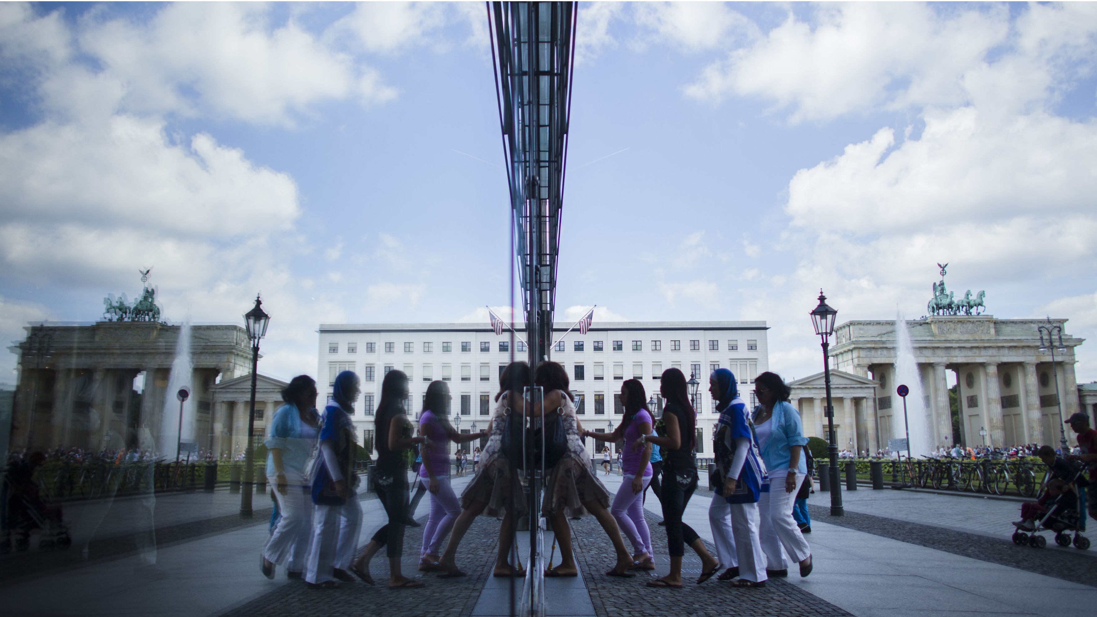 People are reflected in a window as they enter a building in front of Germany's landmark Brandenburg Gate in Berlin, Germany, Thursday, Aug. 23, 2012. Official data show that Germany posted a budget surplus for the first half of this year thanks to its strong labor market, even as other eurozone countries struggle with deficits. (AP Photo/Markus Schreiber)
