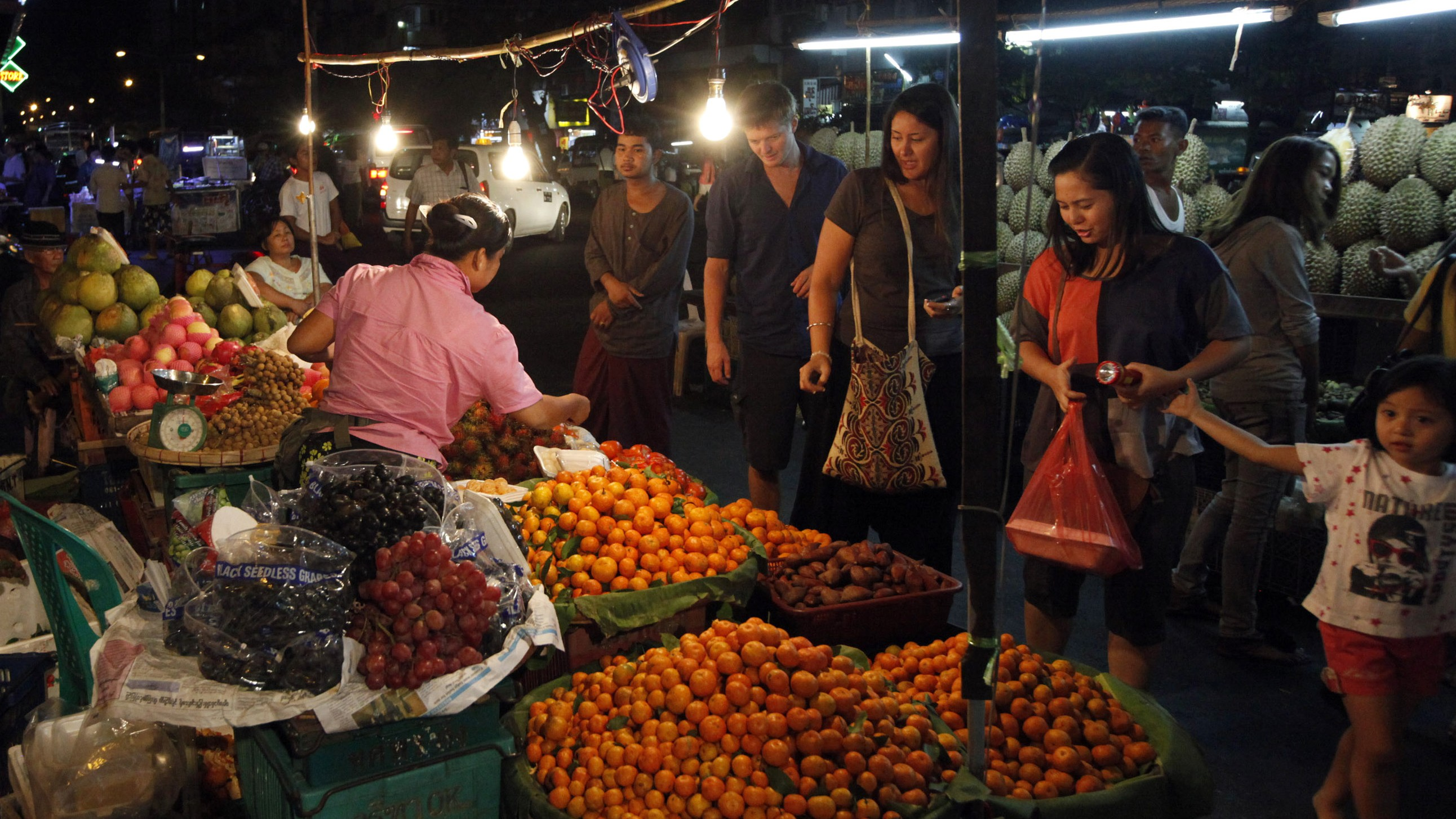 In this photo taken on Wednesday, Jan.16, 2013, customers buy fruits at roadside stall in China town in Yangon, Myanmar. (AP Photo/Khin Maung Win)
