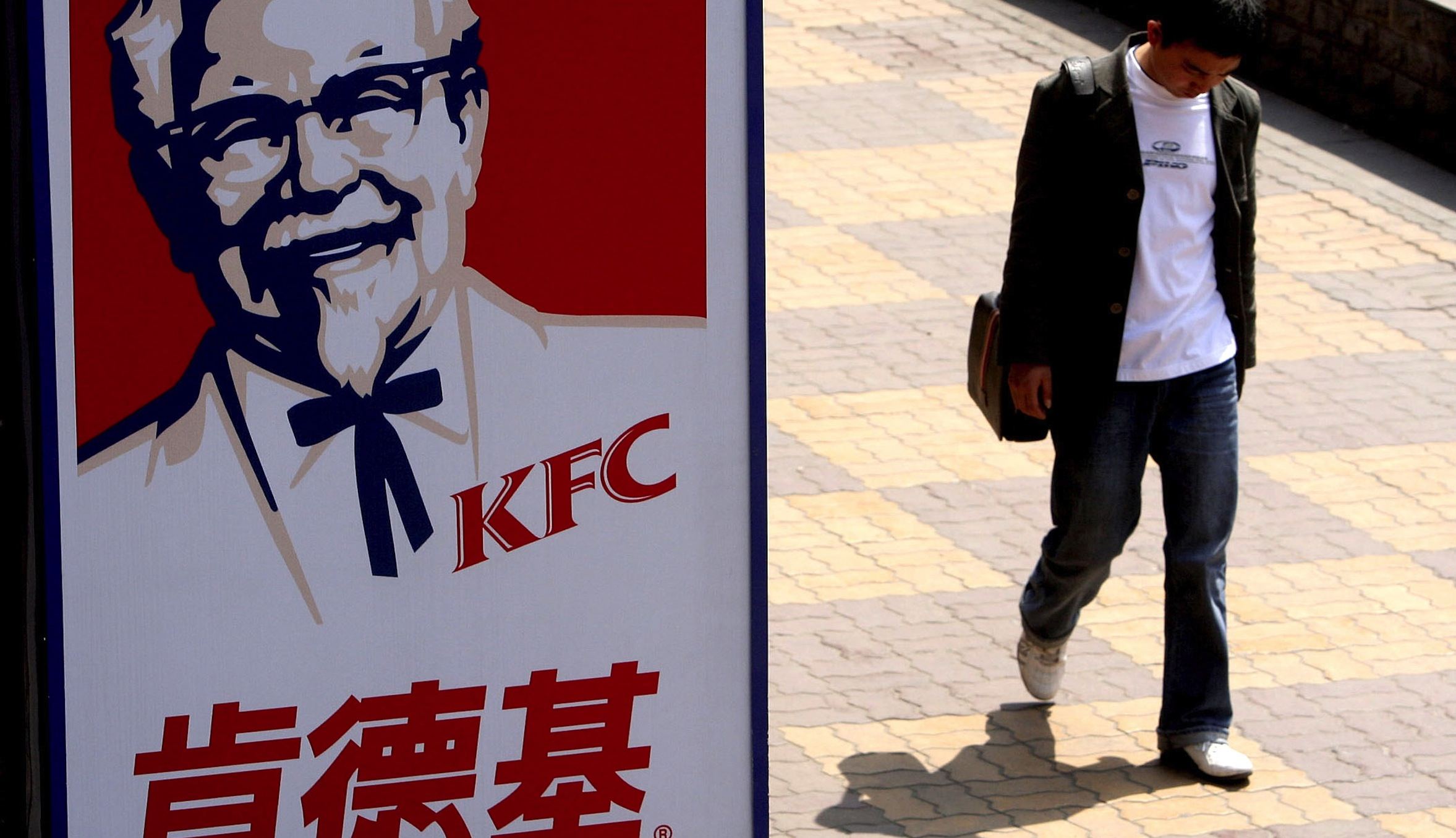 A man walks past a sign for KFC in Shanghai, China.