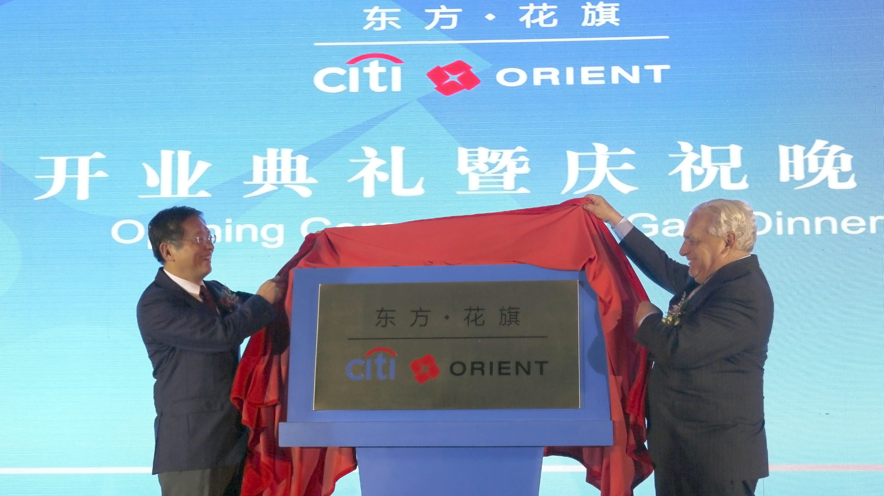 Shanghai Vice Mayor Tu Guangshao, left, and Lewis Kaden, Vice Chairman at Citigroup, right, unveil the plate of Citi Orient Securities Company Ltd Monday Aug. 6, 2012 in Shanghai, China.(AP Photo)