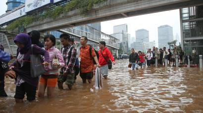 People wade through a flooded street in Jakarta