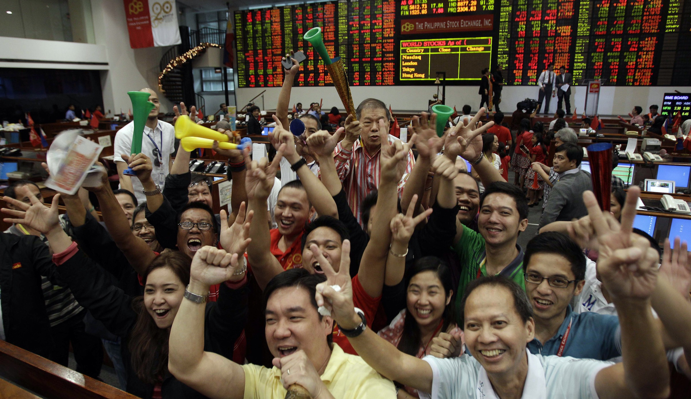 Filipino traders react in front of photographers during the last day of trading this year at the Philippine Stock Exchange in the financial district of Makati, south of Manila, Philippines on Friday Dec. 28, 2012. The Philippine Stock Exchange index was up 0.31% or 17.84 points to close at 5,812.73.