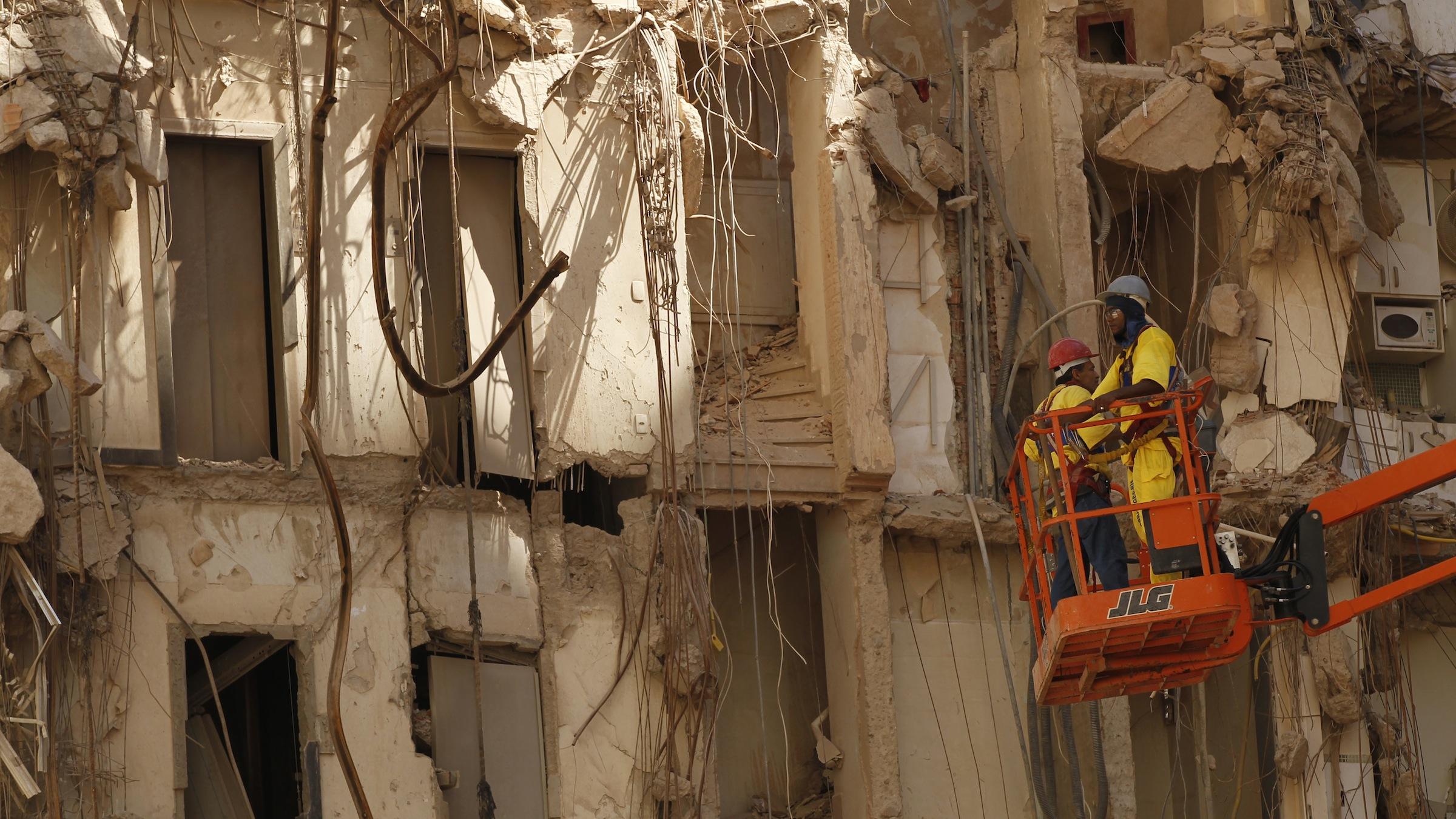 Workers inspect three collapsed buildings in Rio de Janeiro, Brazil, Wednesday Feb. 1, 2012.  A 20-story building collapsed in Rio's center a week earlier, causing the destruction of two smaller ones and killing at least 17 people. The sudden collapse of the enormous buildings in this seaside Olympic city's center along with other accidents involving infrastructure in the past year are contributing to a growing concern about Rio de Janeiro's readiness to host the finals of the 2014 World Cup as well as the 2016 Olympics. (AP Photo/Silvia Izquierdo)
