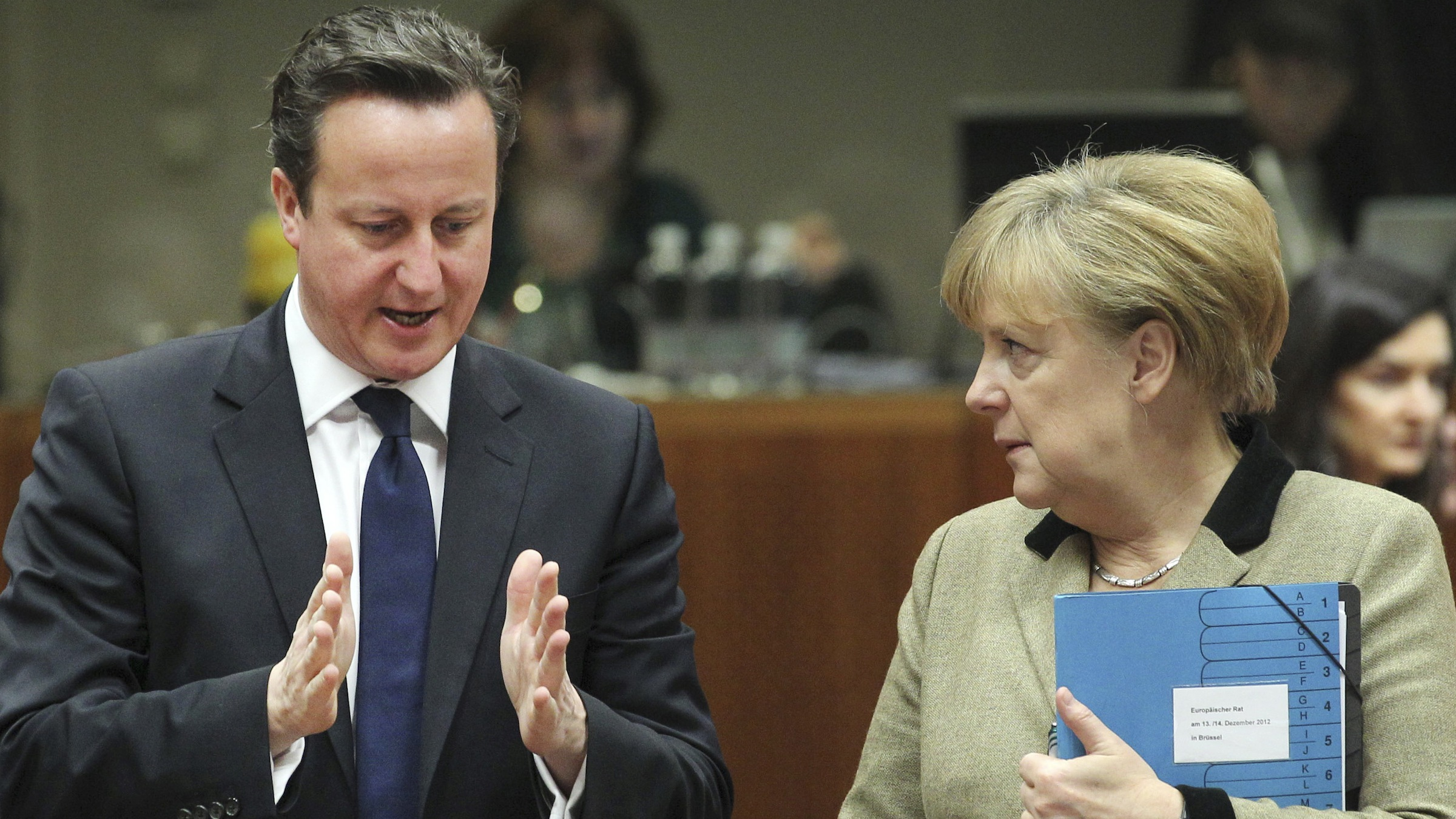 British Prime Minister David Cameron, left, speaks with German Chancellor Angela Merkel during a round table meeting an EU summit in Brussels on Friday, Dec. 14, 2012. France and Germany have had more than their share of difference over the past few months, but this week at long last the two countries were able to find a compromise that allowed the European Union to realize a deal on a banking union. (AP Photo/Yves Logghe)