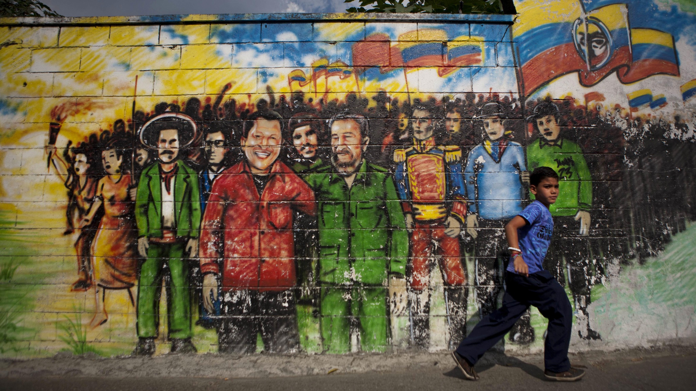 """A youth walks past a mural depicting Venezuela's President Hugo Chavez, center left in a red shirt, standing with Cuba's leader Fidel Castro in Caracas, Venezuela, Wednesday Feb. 22, 2012. Chavez told Venezuelans on Tuesday that doctors in Cuba had over the weekend found a lesion in the same place where they removed a cancerous tumor last year. Chavez, who hopes to extend his 13 years in power with another six-year term in the Oct. 7 elections, said the probability is high that the lesion is malignant and that he will likely need radiation therapy. Also in the mural are Venezuela's independence hero Simon Bolivar, third from right, Cuba's revolutionary hero Ernesto """"Che"""" Guevara, between Chavez and Castro, and Mexico's revolutionary hero Pancho Villa, left in hat. (AP Photo/Ariana Cubillos)"""