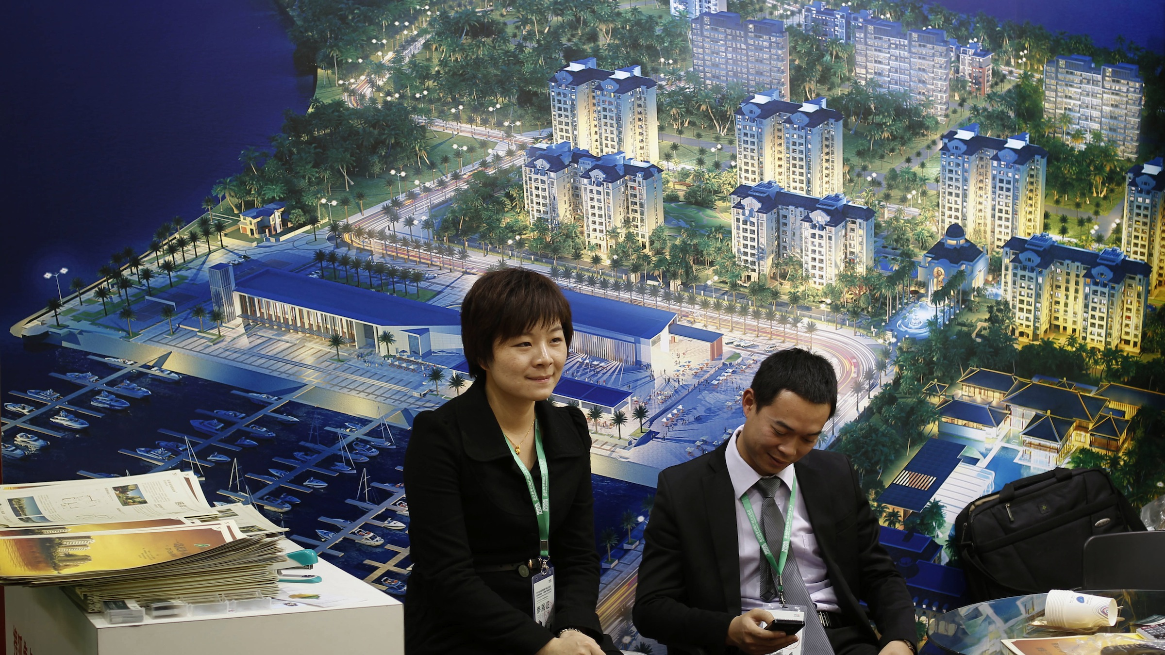 Sales personal waiting for homebuyer next to a billboard show seaside  residential apartment project during a real estate fair in Beijing, China, Thursday, April 5, 2012.  (AP Photo/ Vincent Thian)
