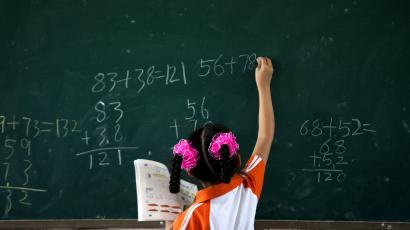 A girl writes on a chalkboard during a math class at Dongba Experimental School, a school for the children of migrant workers, in Beijing Thursday, Aug. 25, 2011. The school has received multiple warnings from the government that it will be demolished later this week if it doesn't close.