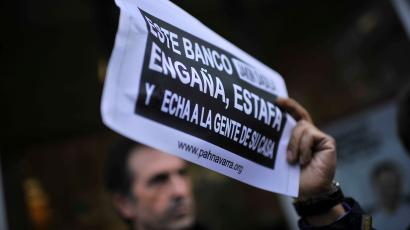A Spanish protester holds up a sign criticizing a bank