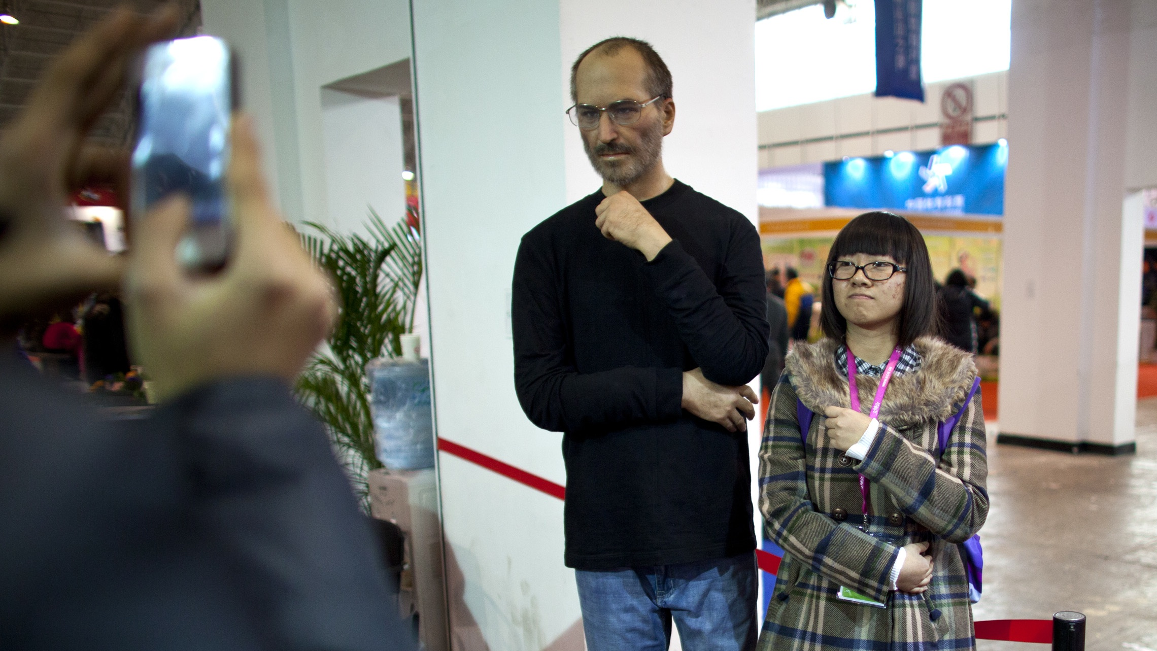A woman poses for photos with a silicone rubber sculpture of late Apple co-founder Steve Jobs at a cultural and creative industry expo in Beijing, China, Saturday, Dec. 22, 2012. (AP Photo/Alexander F. Yuan)