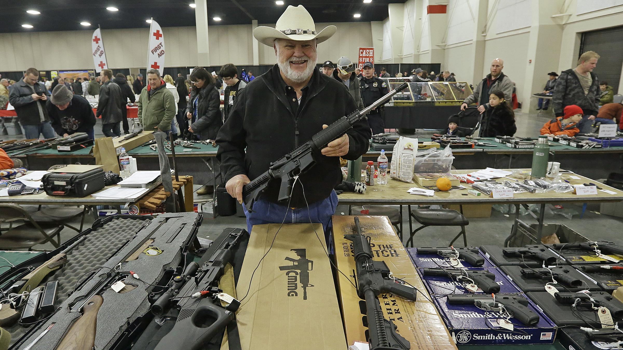 Ken Haiterman, of Pioneer Market, holds a CMMG 5.56mm AR 15 during the 2013 Rocky Mountain Gun Show Sunday, Jan. 6, 2013, in Sandy, Utah.