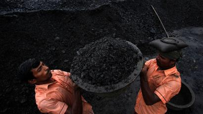 Laborers load coal onto a truck at a coal depot in Gauhati, India