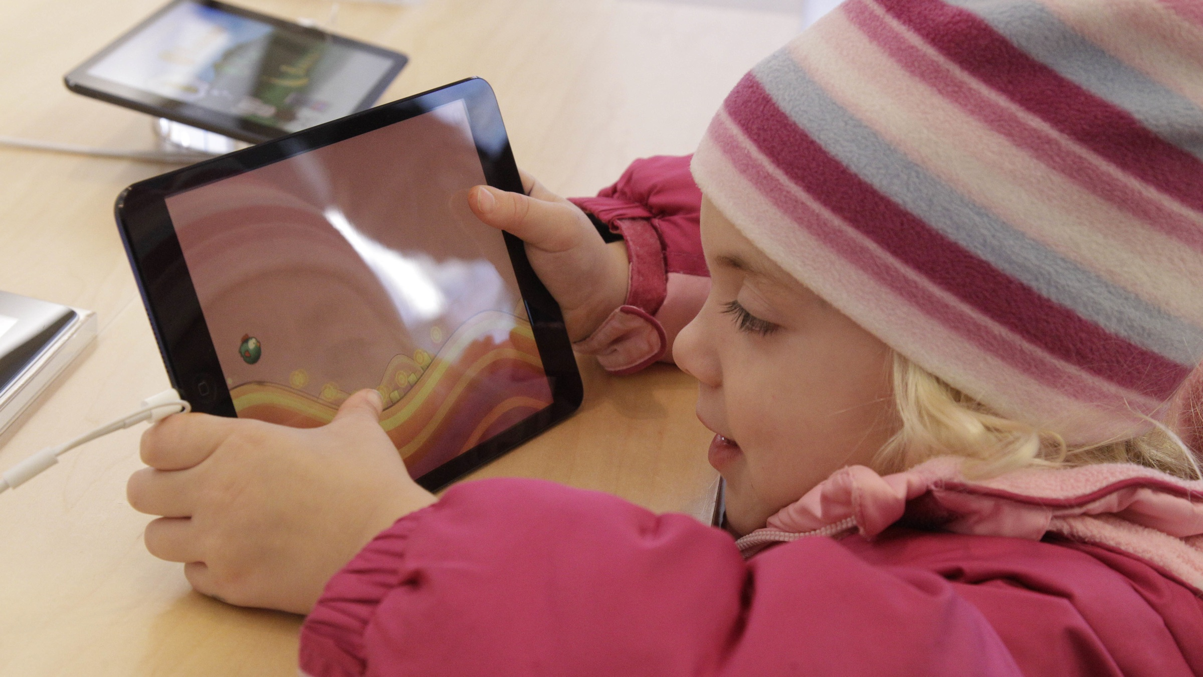 Julie Ianeloo, 5, check out the new Apple iPad mini at the Apple store on Michigan Ave. Friday, Nov. 2, 2012 in Chicago. Apple's new 7.9 inch tablet went on sale at 8:00 A.M. CDT at the store. (AP Photo/M. Spencer Green)