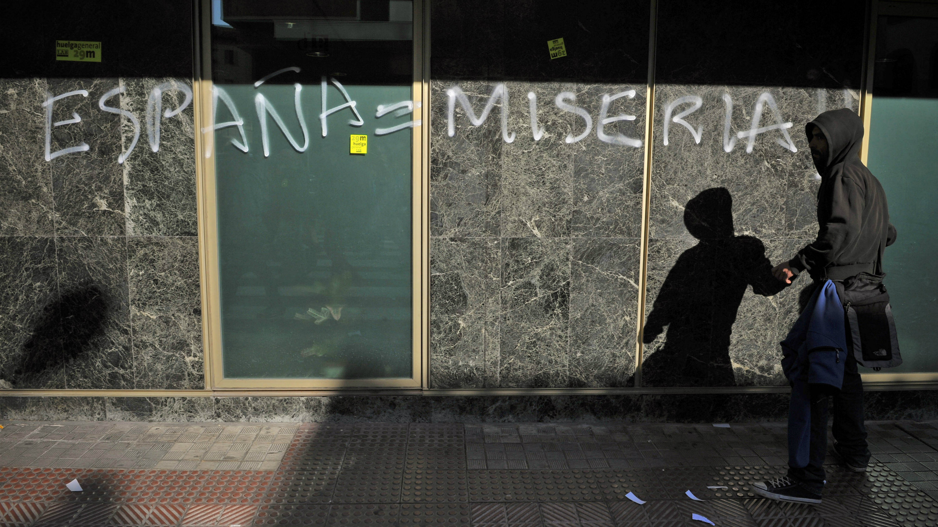 """A man in front of graffiti on a building in Spain reading """"España = Miseria"""""""