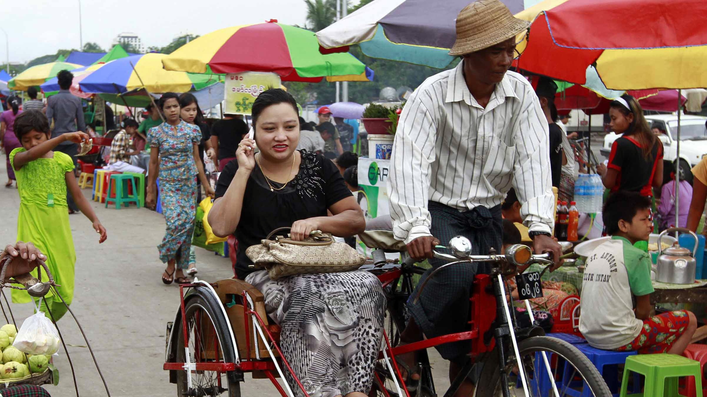 In this photo taken on Saturday, May.5, 2012, a Myanmar uses her cell phone as she rides a trishaw at a local bazaar in Yangon, Myanmar. (AP Photo/Khin Maung Win)