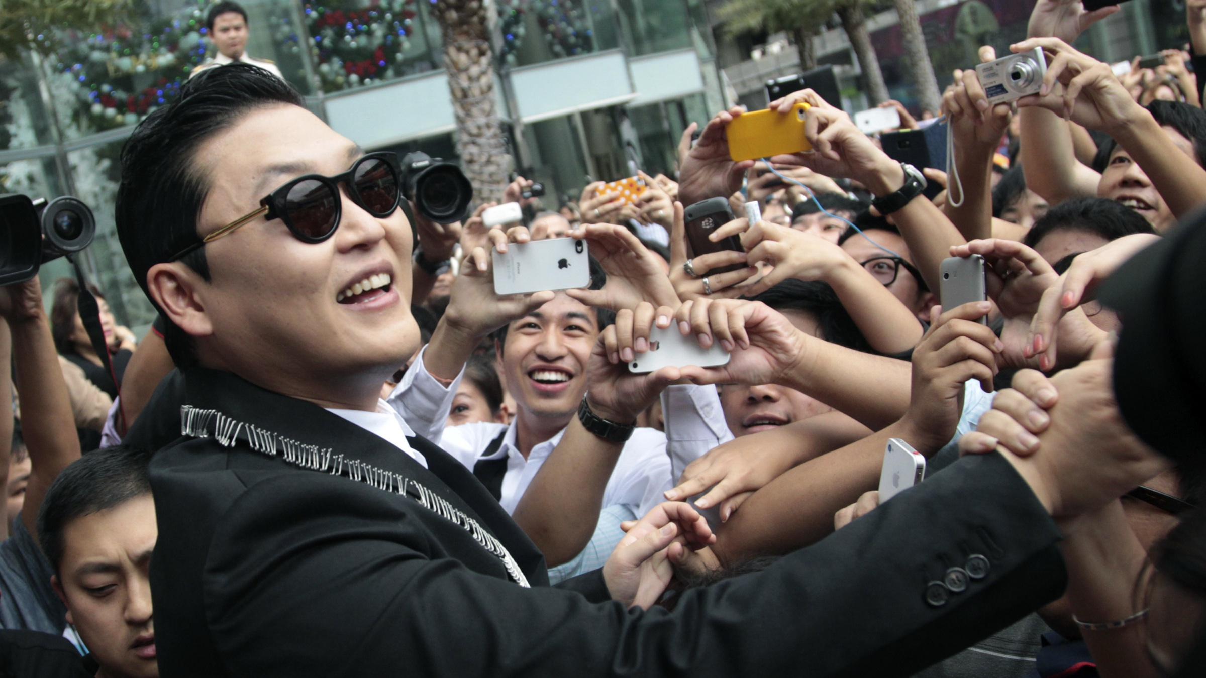 """South Korean rapper Psy, """"Gangnam Style""""shake hands  his Thai fan after  press conference his concert in Bangkok, Thailand, Wednesday, Nov. 28, 2012.(AP Photo/Sakchai Lalit)"""