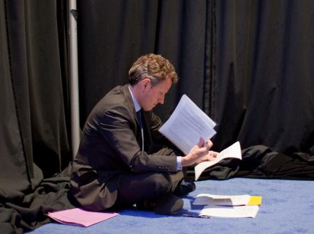 Treasury Secretary Timothy F. Geithner sits on the floor and reviews notes before President Barack Obama's press conference at the G20 Summit in Toronto, Canada.