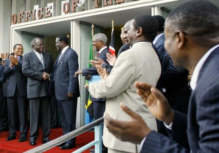 Kenyan President Mwai Kibaki, second from left, and opposition leader Raila Odinga, third from left, shake hands after signing a power-sharing agreement .