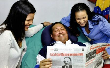 Hugo Chávez with his daughters, holding a copy of Granma.