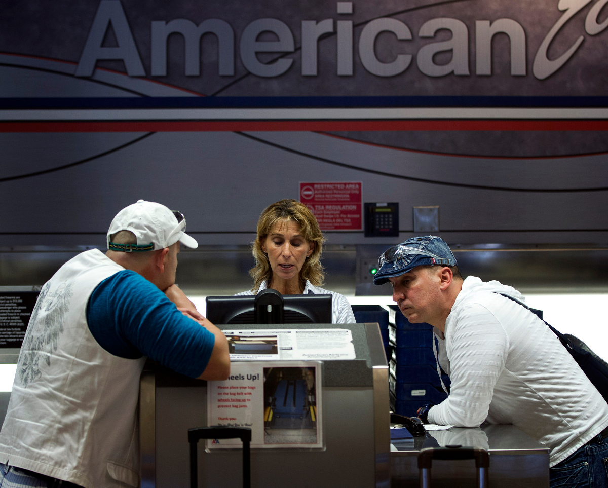 Two unidentified American Airlines passengers talk to a customer service representative, center in Miami.