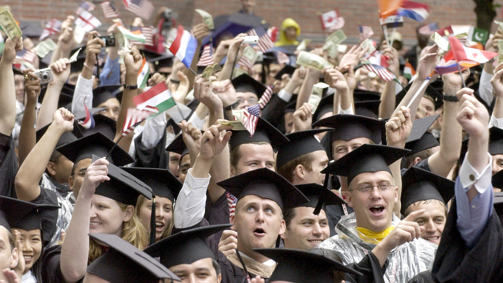 Business school graduates cheer while waving dollar bills and flags during Harvard University's 353rd commencement ceremonies, Thursday, June 10, 2004, in Cambridge, Mass. (AP Photo/Michael Dwyer)