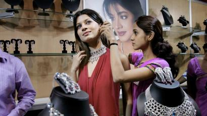 A sales clerk assists a model in wearing jewelry at a jewelry and gem exhibition in New Delhi, India