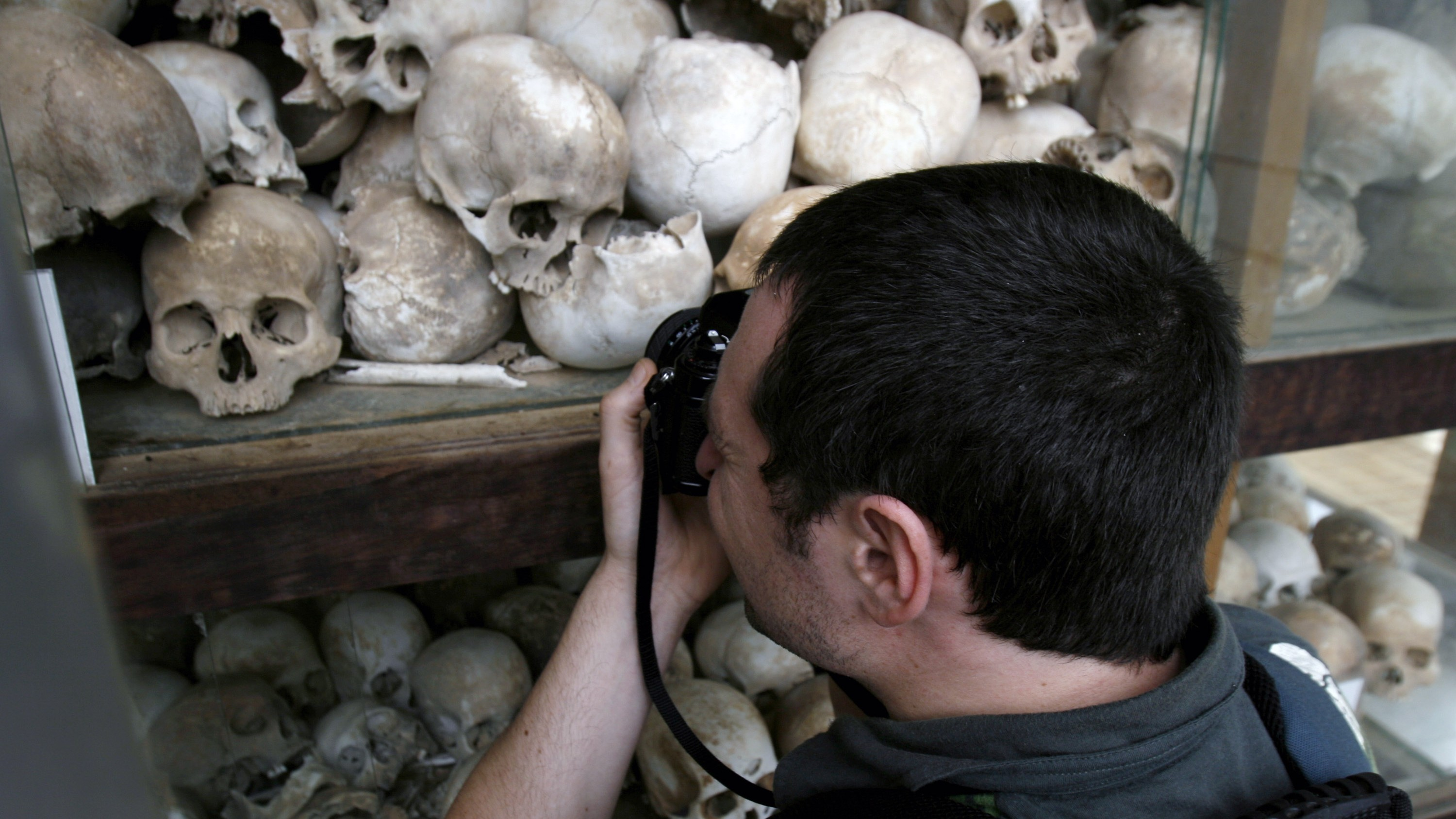 """A Westerner tourist man takes picture of human skulls at Choeung Ek killing field in Phnom Penh, Cambodia, Thursday, Feb. 26, 2008. The former head of a notorious Khmer Rouge torture center was moved to tears Tuesday when he was taken by Cambodia's genocide tribunal to the scene of his alleged crimes, a mass grave site that was one of the country's notorious """"killing fields."""" (AP Photo/Heng Sinith)"""