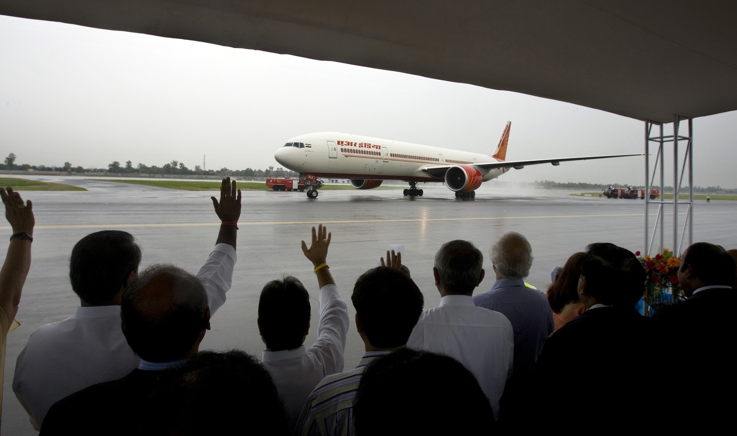 An Air India aircraft taxies as officials wave after landing on the newly constructed third runway at the  Indira Gandhi International Airport  in New Delhi, India, Thursday, Aug. 21, 2008. Indian officials inaugurated the country's longest runway Thursday, hoping it will ease conditions at New Delhi's chronically congested Indira Gandhi International Airport. (AP Photo/Gurinder Osan)